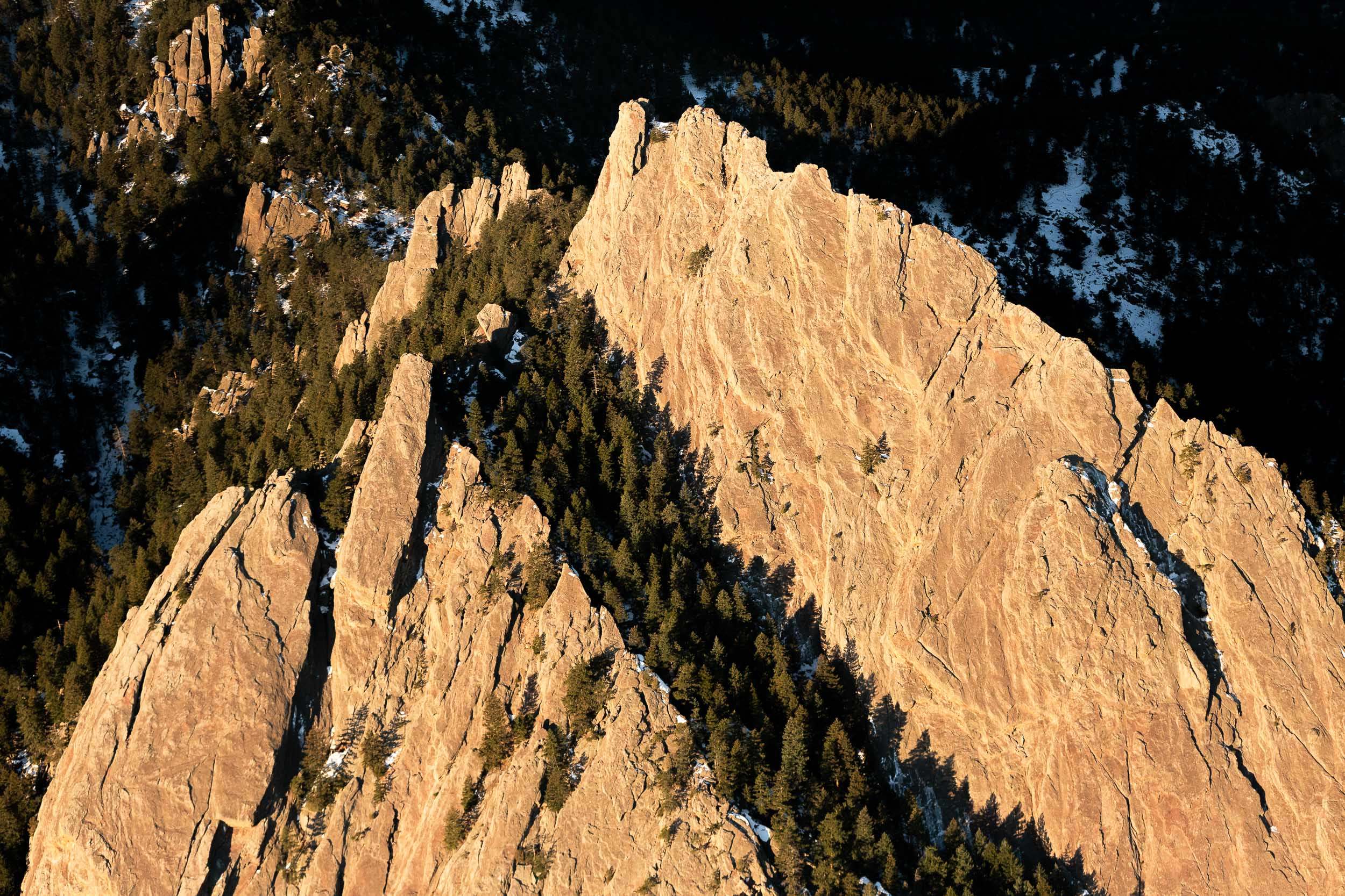 An aerial photograph of the first and second Flatiron rock formation in Boulder, Colorado in the Rocky Mountains on a cold, snowy winter morning just after sunrise.