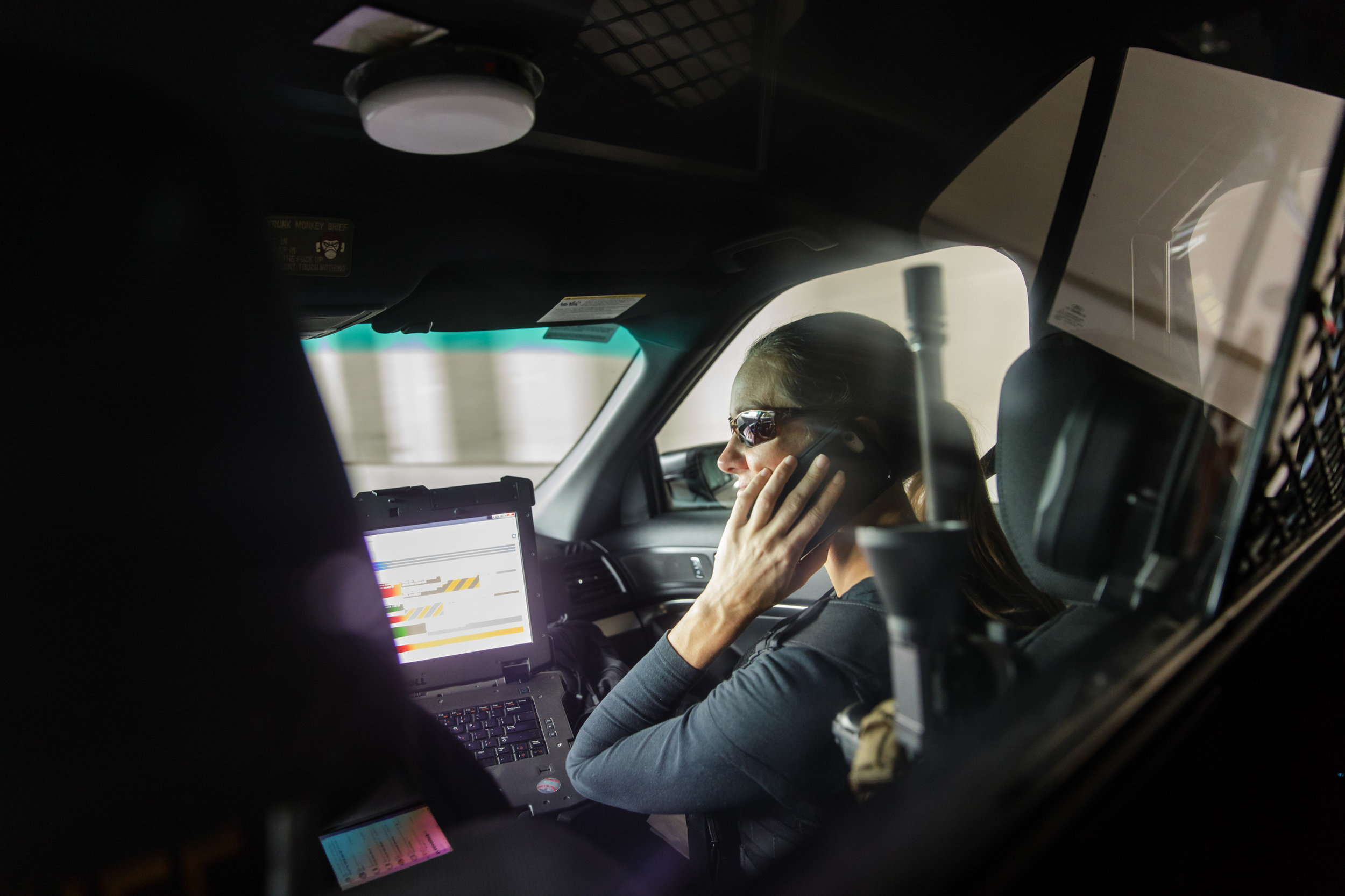 Lauren Rainbow taking a phone call in the front seat of a police car.    CREDIT: LEAH NASH FOR FINDING FIXES »