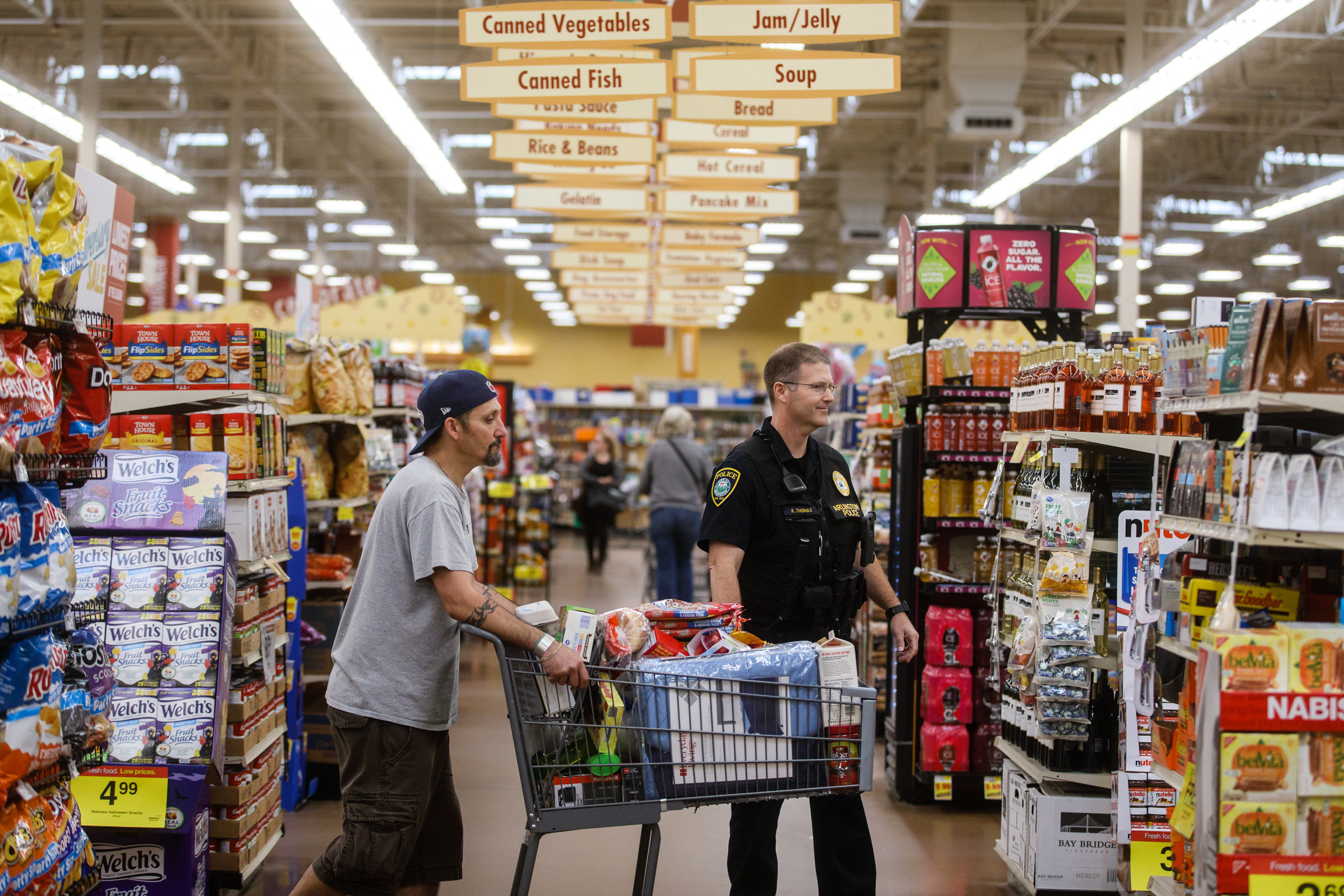 An Arlington police officer helping a man gather groceries and personal items at a Fred Meyer grocery store.    CREDIT: LEAH NASH FOR FINDING FIXES »