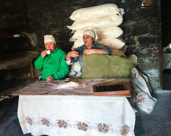 At first I thought we were going to annoy these lavash-baking ladies by getting in the way. But they were not only gracious with information, they kept feeding us and serving us  soorj , Armenian coffee. That's a box of chocolates on the table. One of the women is fixing the  batat, the  pillow-like thing they use to stick the lavash to the walls of the tonir with a firm  whomp .