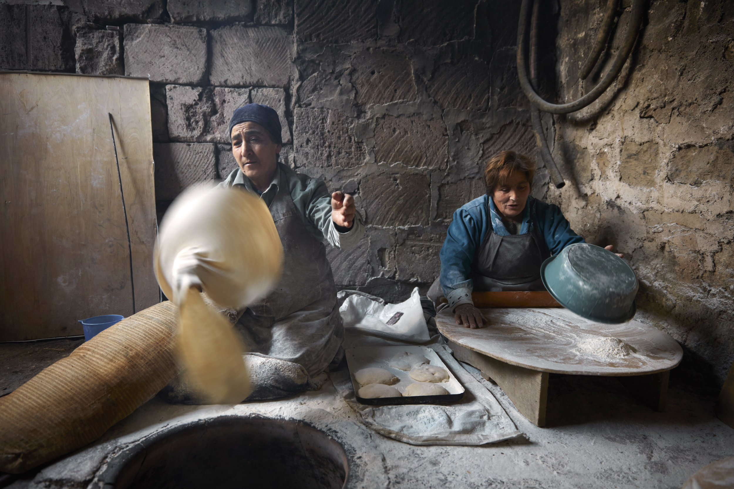 In Yeghvard, each neighbor tool on a different responsibility around the tonir: some rolled the dough, some removed it from the walks of the tonir. But the most challenging job was spinning and stretching the dough out into a thin sheet.