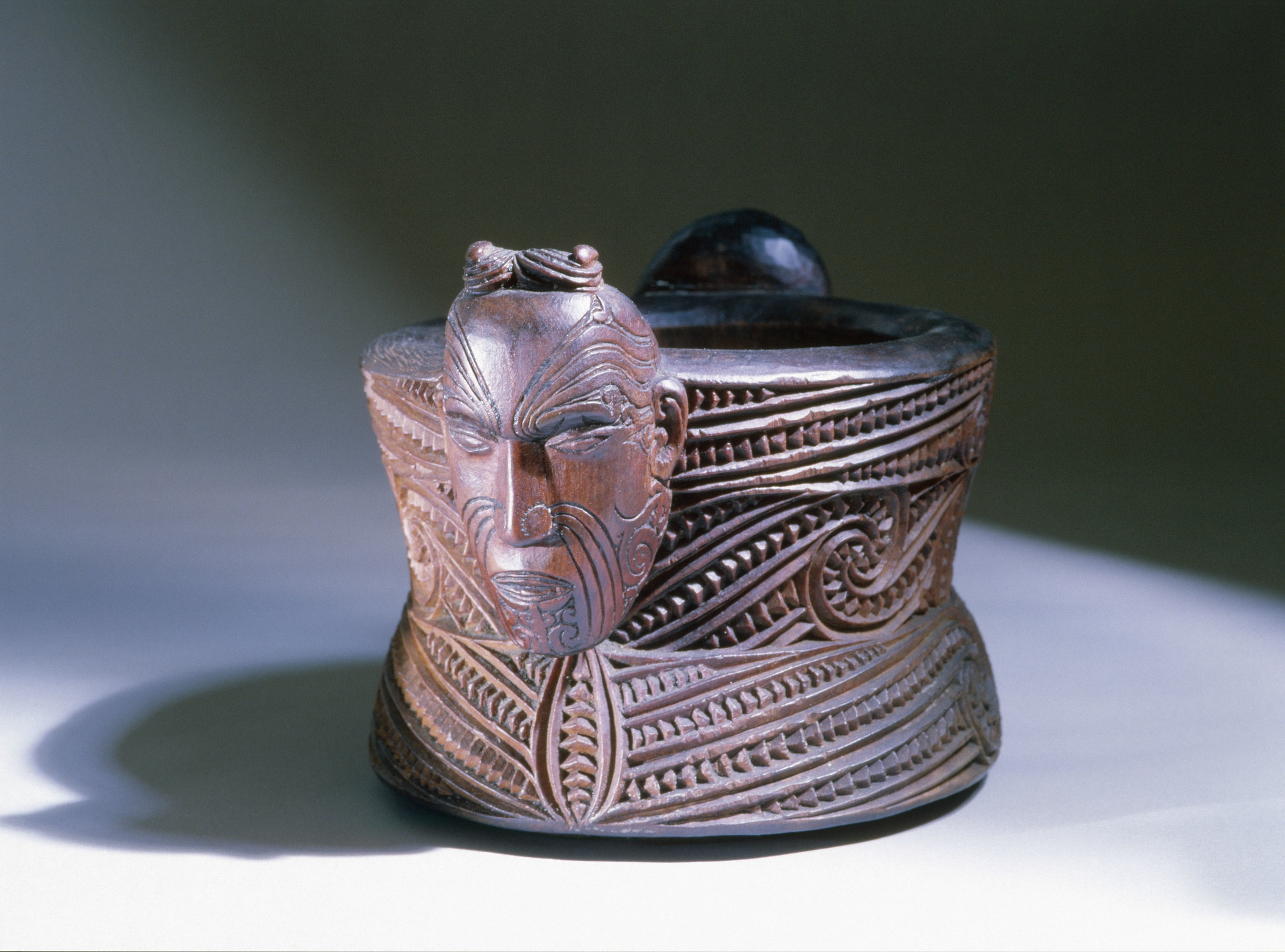 A oval-lidded wooden box with scrolling on the sides and a carved male and female heads as suspension lugs at each end.   Late 19th - Early 20th century   Inv. #: 55405060 © Werner Forman Archive / Napier Museum, New Zealand
