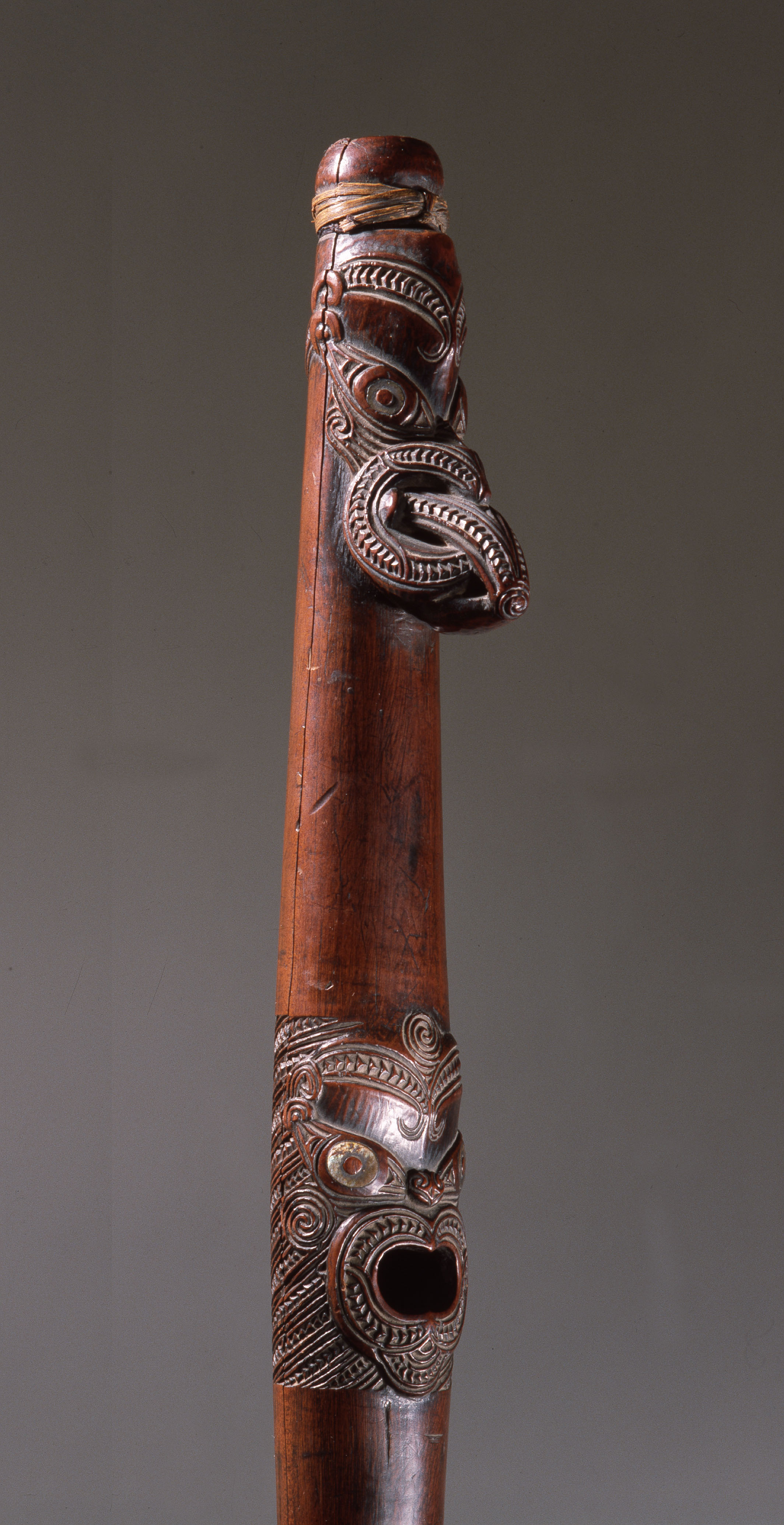 Putorino, or flute trumpet carved with three aggressive faces. It may be played as a flute by blowing across the top, or used as a trumpet, but has only one note, modified by closing the centre hole. Putorino were used to signal the return of a chief to the village or to accompany lyrically sung poems from the Maori's rich oratorical traditions.   18th - 19th century   Inv. #: 55406972 © Werner Forman Archive / Courtesy of Entwistle Gallery, London.