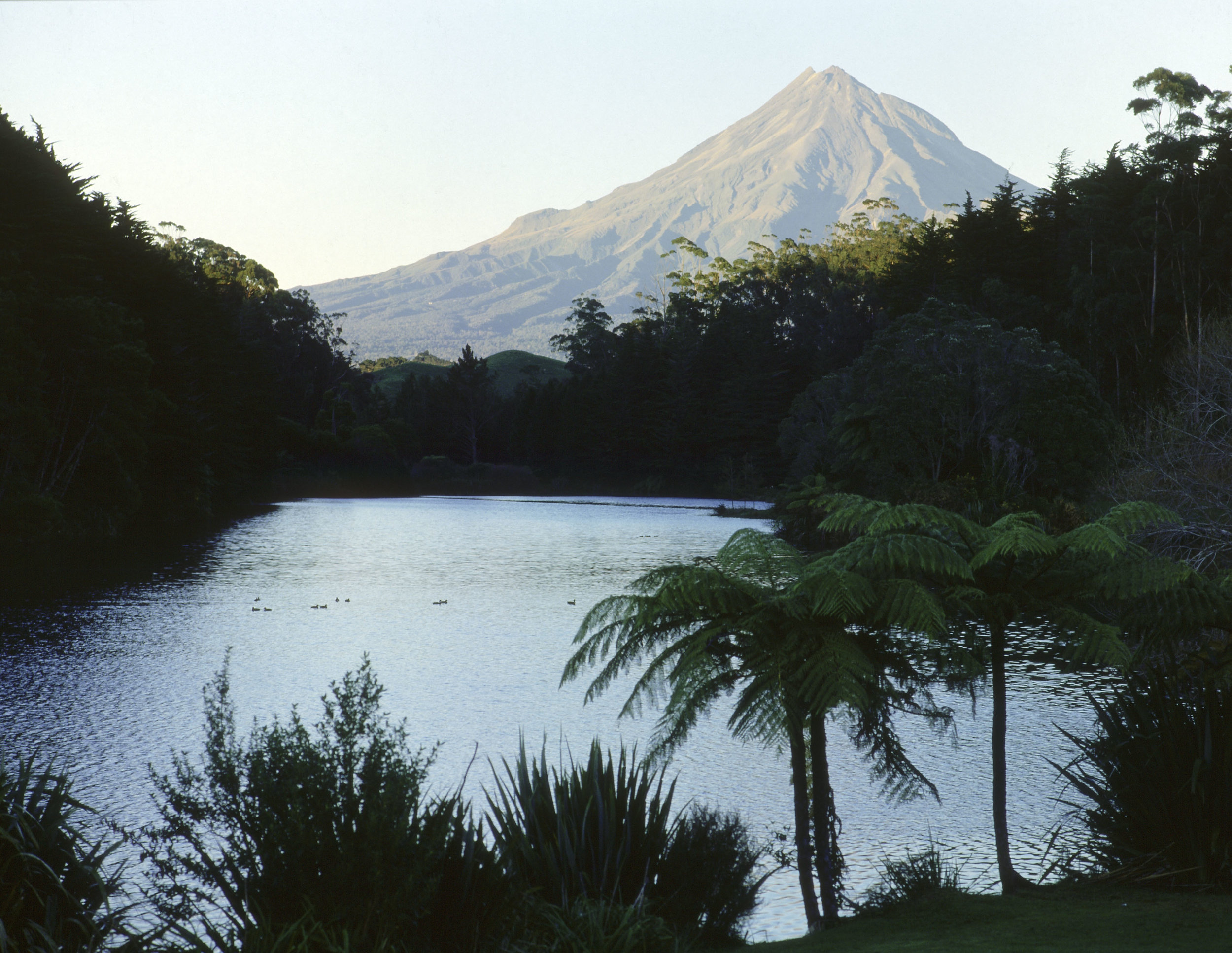 Mount Egmont as seen from Lake Wangamahoe. Normally covered in clouds, the great volcano is the subject of many Maori myths, some of which that tell the story Mt. Egmont's love for the female volcano, Ruapehu. Lake Wangamahoe, North Island.   Inv. #: 55405085 © Werner Forman Archive