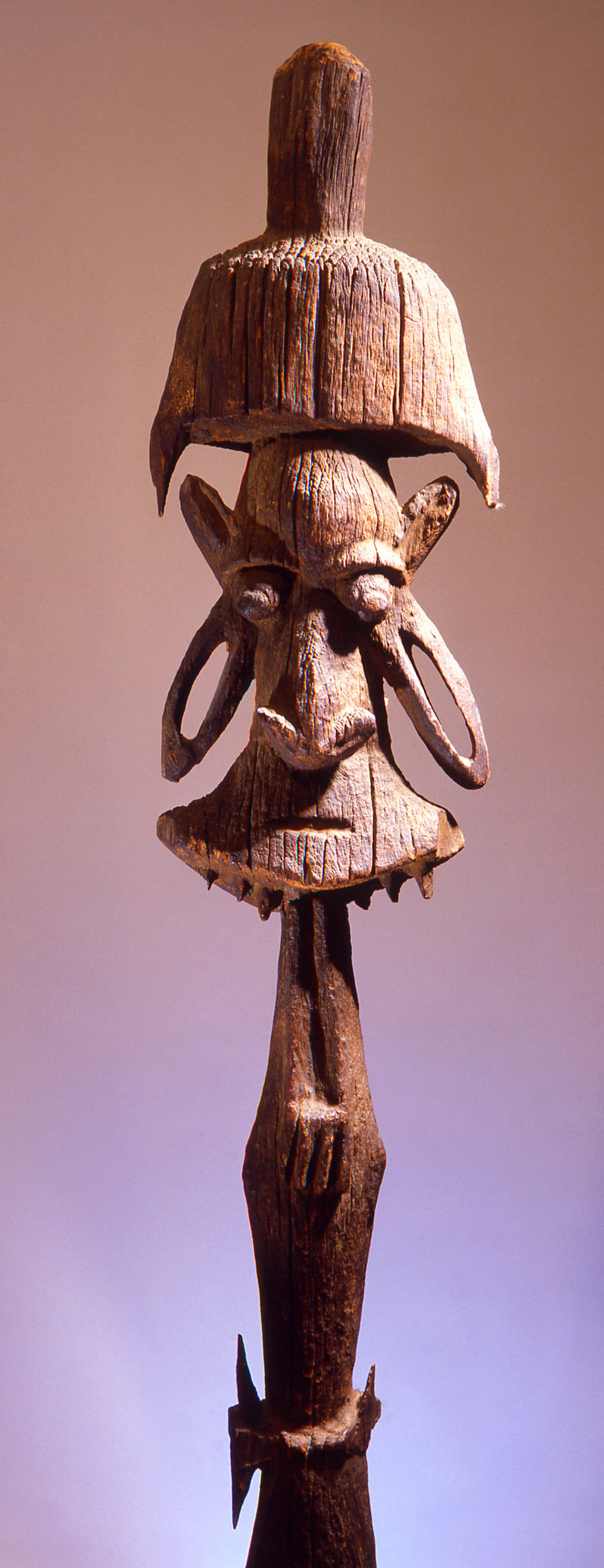 Roof finial post from a men's meeting house. New Caledonian carving employed a complex form of split representation where details of the head are separated into flat segments and the rear of the head is spread out above the face. Country of Origin: New Caledonia. Culture: Oceanic. Material Size: Wood. Credit Line: Werner Forman Archive / Private Collection.