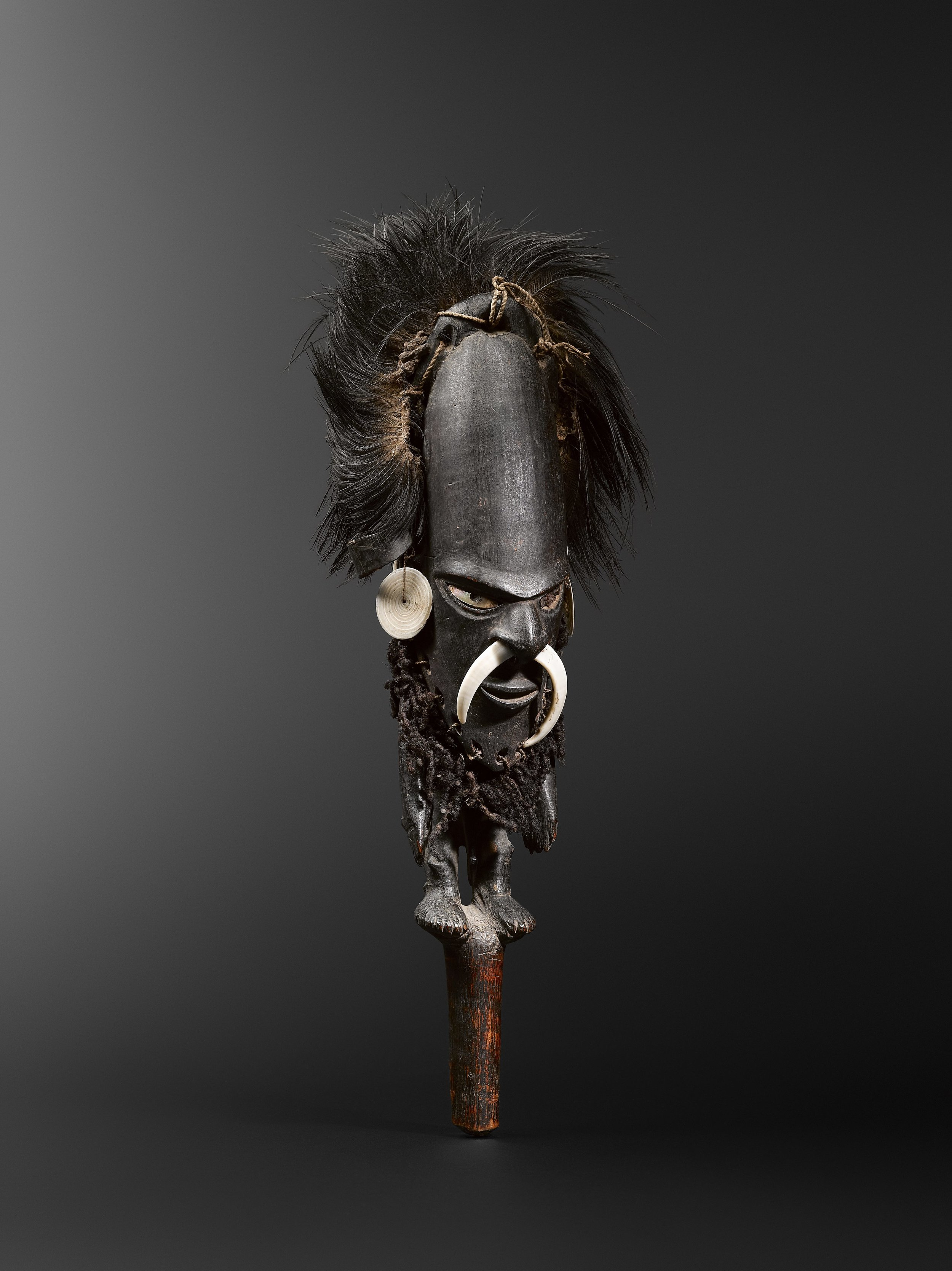 Flute stopper,  wusear.  Mundugumor / Biwat. Yuat River. Wood, cassowary feathers, fibre, boars' tusks, turtle shell, Conus and mother-of-pearl shells, human hair and pigments. 50 cm. Bisseling Collection, The Hague. Jef Vanderstraete, Lasne, Belgium. © Hugues Dubois, Brussels/Paris
