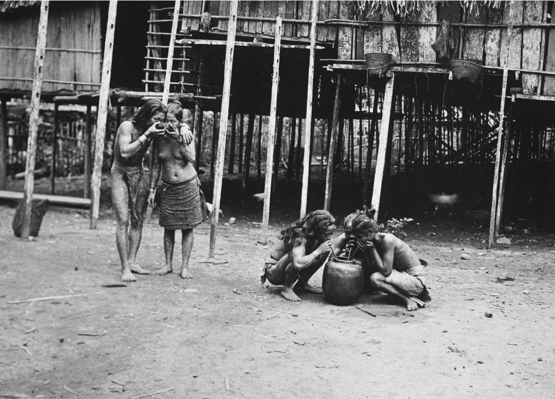 Group of Dayaks drinking in front of a longhouse. 1910-1925. © Tropenmuseum | The Netherlands