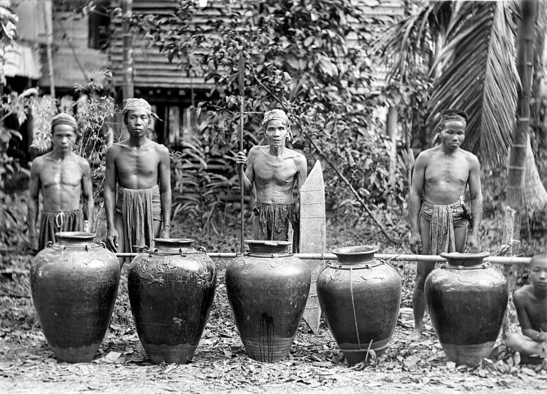 Four Dayak men standing behind 5 large jars belonging to the village head of Pangkoh, Central Kalimantan. Circa 1925. © Tropenmuseum | The Netherlands