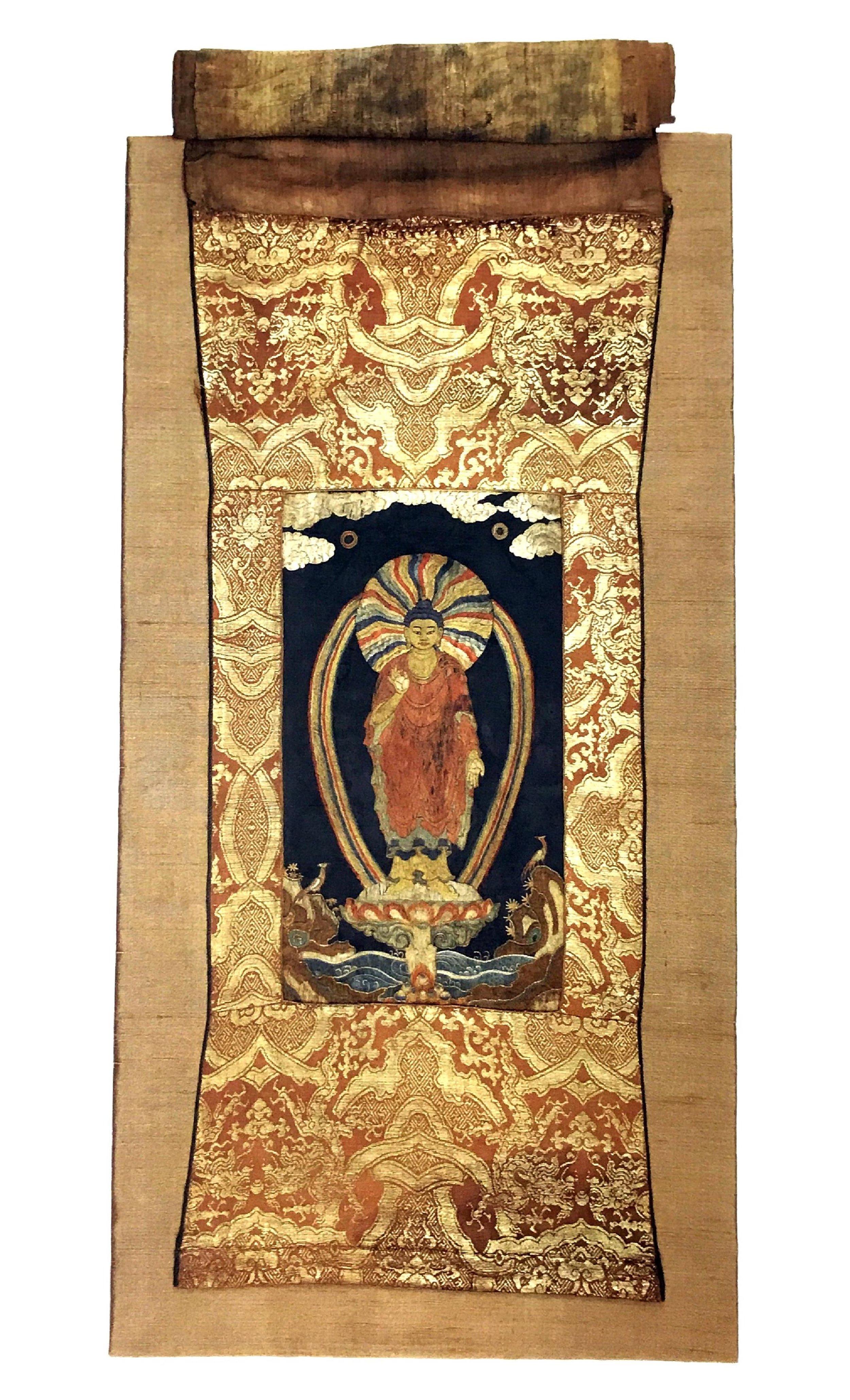 Thangka of Shakyamuni Buddha.  China, 15th century. Silk satin (embroidered); brocade border and veil. Collection of Chris Hall. Image courtesy of Asian Civilizations Museum.