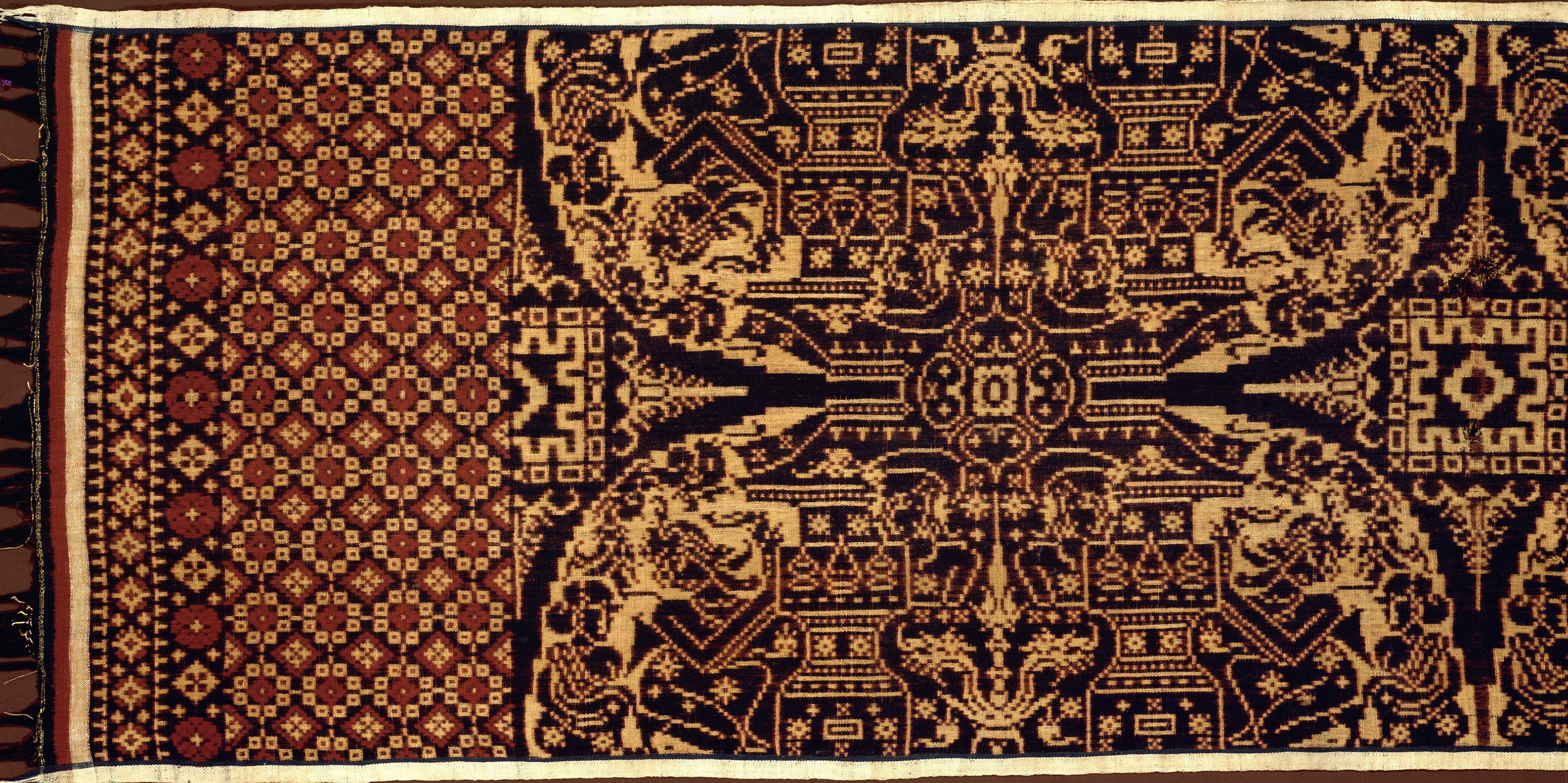 Geringsing, double ikat. The design shows in its offering scenes specific Balinese temple architecture in great detail. Offering vessels are clearly discernible. Country of Origin: Indonesia. Culture: Bali. Date/Period: 20th C. Place of Origin: Tenganan Pageringsingan. Material Size: Cotton. Credit Line: Werner Forman Archive/ Museum fur Volkerkunde, Basel.