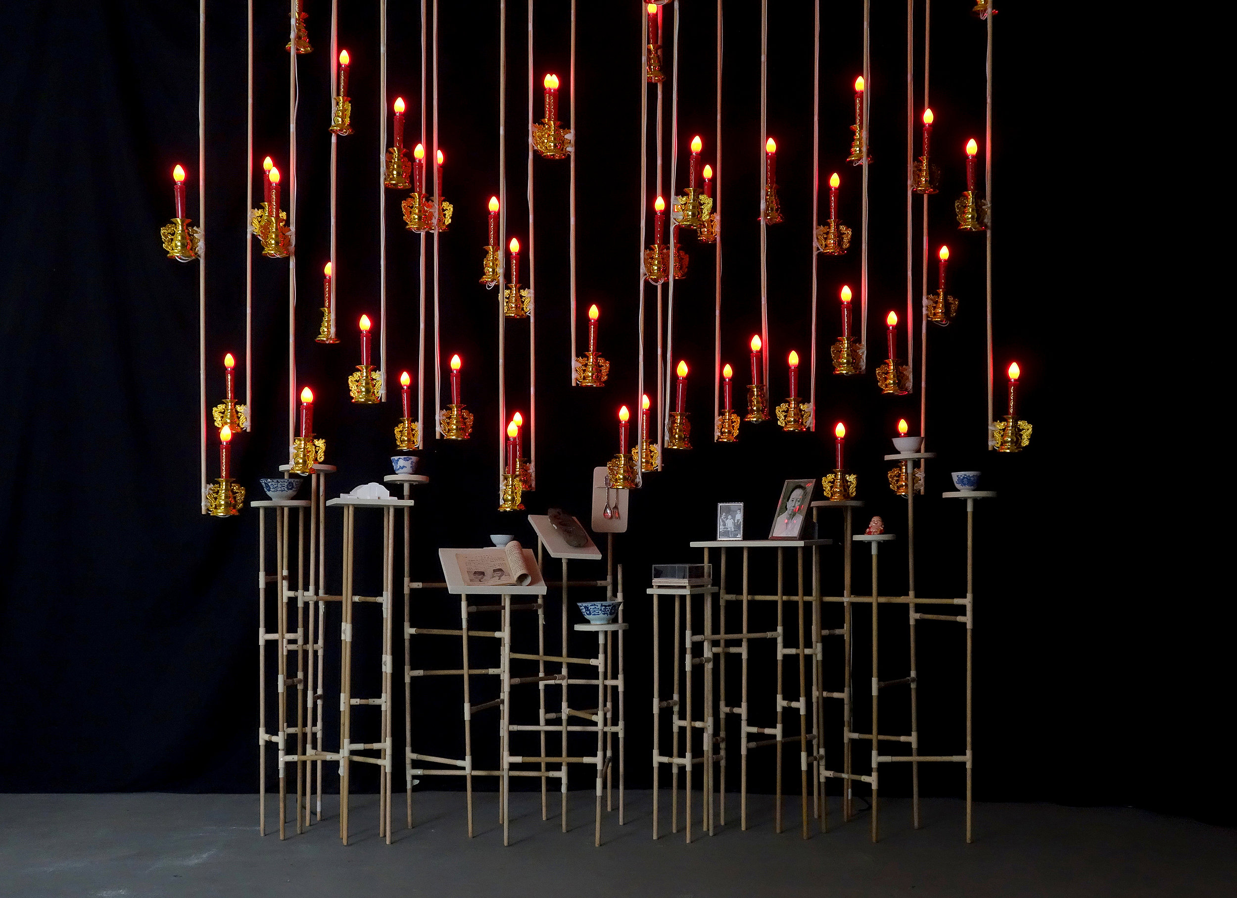 FX Harsono    Gazing on collective memory  2016 wood, found objects, books, ceramic bowls, wooden butter mould, wooden cookie mould, metal spoons, 3D digital prints, framed photographs and electric candle lights National Gallery of Australia, Canberra Purchased 2018 © FX Harsono