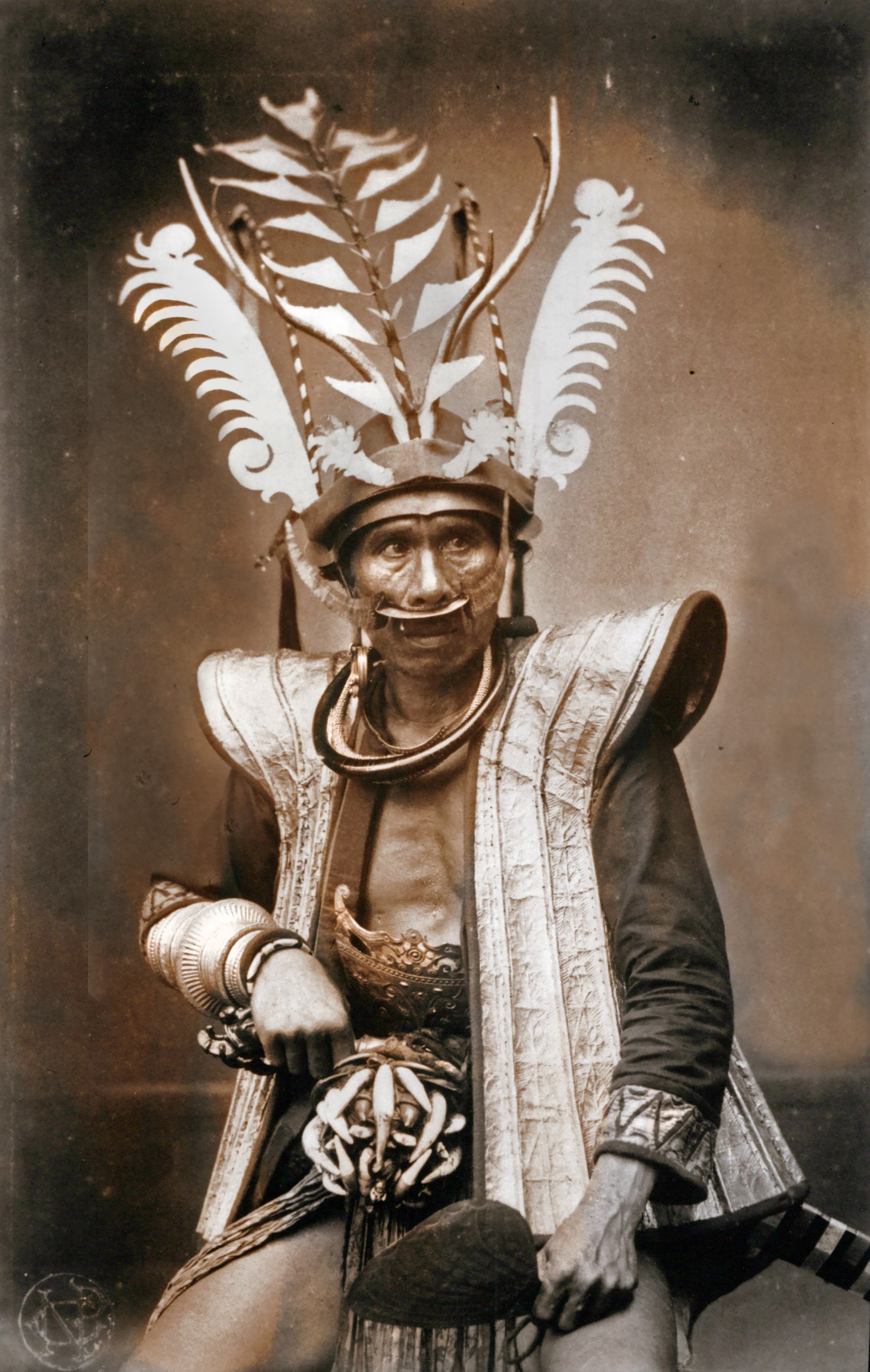 Wealthy nobleman, wearing magnificent gold jewelry showing his high rank and status within Nias community. His jacket,  g-orobána'a , is covered with strips of ornamented gold leaf, sewn to a base of buffalo leather. Above the sword he wears a beautifully decorated plate, South Nias. (Photograph C.B. Nieuwenhuis ca. 1915.)