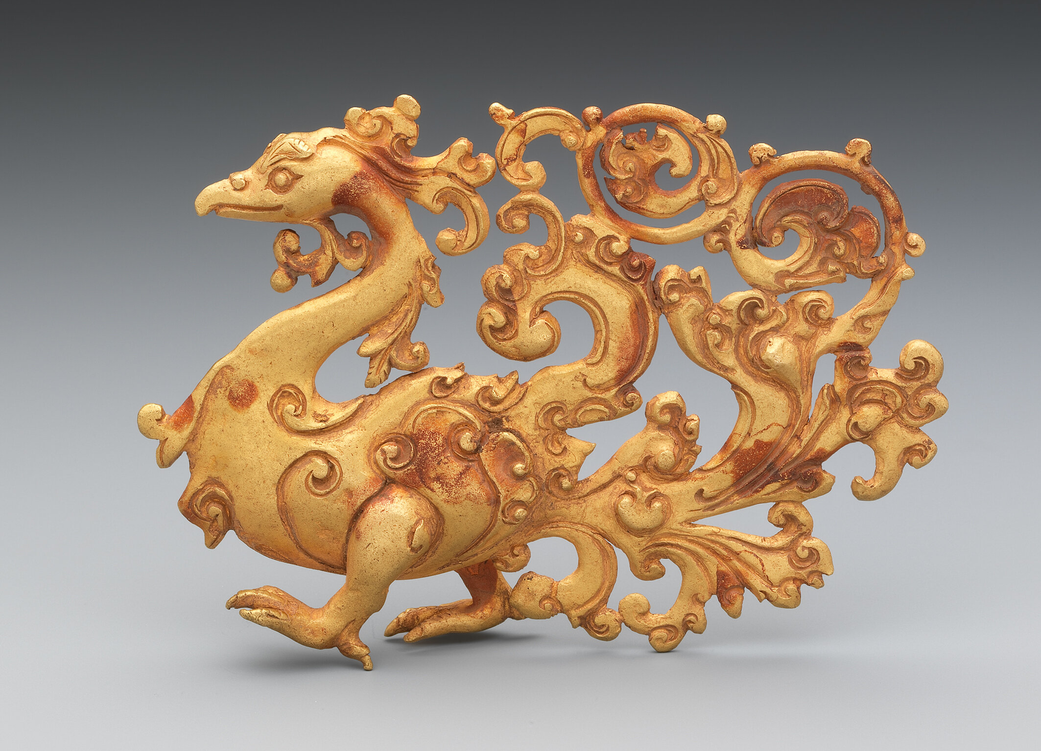 Stolzierender Vogel Java, 7.–15. Jh. 257 g, h: 74 mm, w: 104 mm Das Relief eines stolzierenden Vogels, vermutlich ein Pfau, beweist ein extrem hohes Niveau der Goldschmiedearbeit und die atemberaubende Schönheit der Gestaltung. Während der Vogelkörper mit dem gebogenen Schnabel und den langen Beinen naturalistisch dargestellt ist, wurde das Schwanzgefieder ornamental mit Arabesken und gewundenen Blattformen gestaltet. © Mauro Magliani