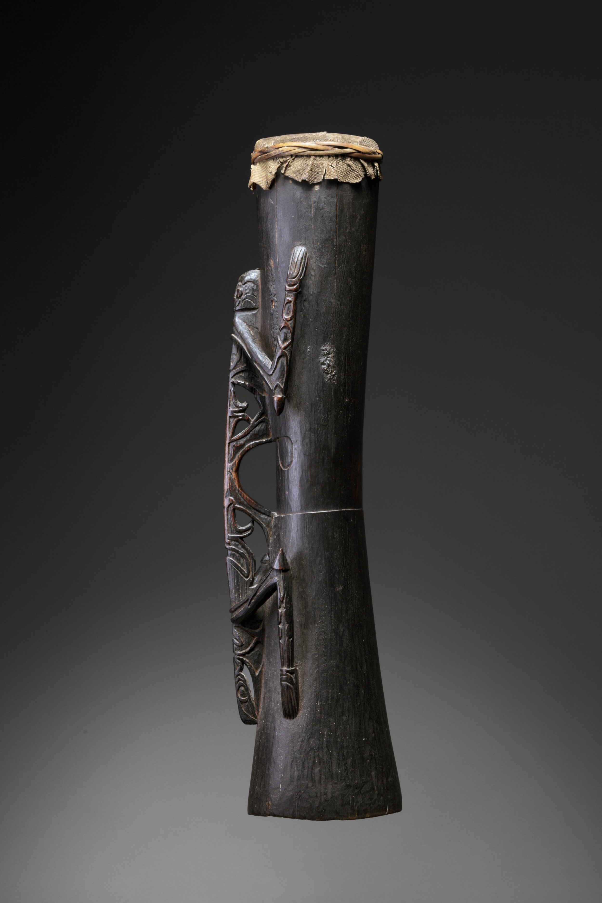 Drum - Asmat, Papua Barat, Indonesia - Material: Wood, Rattan, Lizard Skin - Height 88 centimeters - Provenance: This Asmat drum was, on the occasion of his departure from Asmat, donated to J.H.M.C. Boelaars MSC, by the staff of the diocese Agats, as a token of appreciation for his ethnographic research in the Asmat area. Photo Jan van Esch