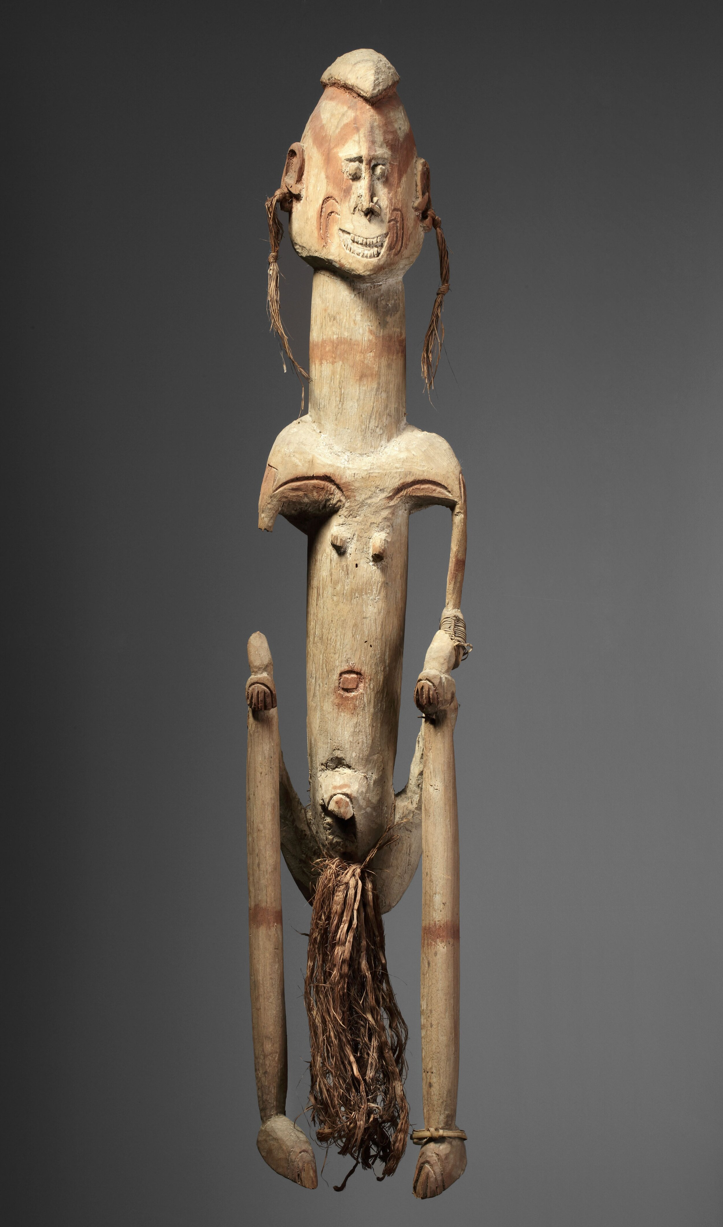 """Ancestor figure J, accompanied by a document typed by the collector indicating: """"Female Figure. Left hand on knee. Missing right arm. Legs straight down. H: 87 cm. Soft wood and light. Originally painted with lime. Incised lines painted red; navel also painted, bands around the legs and painted lizard figure on back. Purchased at the MSC missionary house in 1950. Collected by Father Viegen ... Noordwest River. Private collection. Photo: Jan van Esch"""