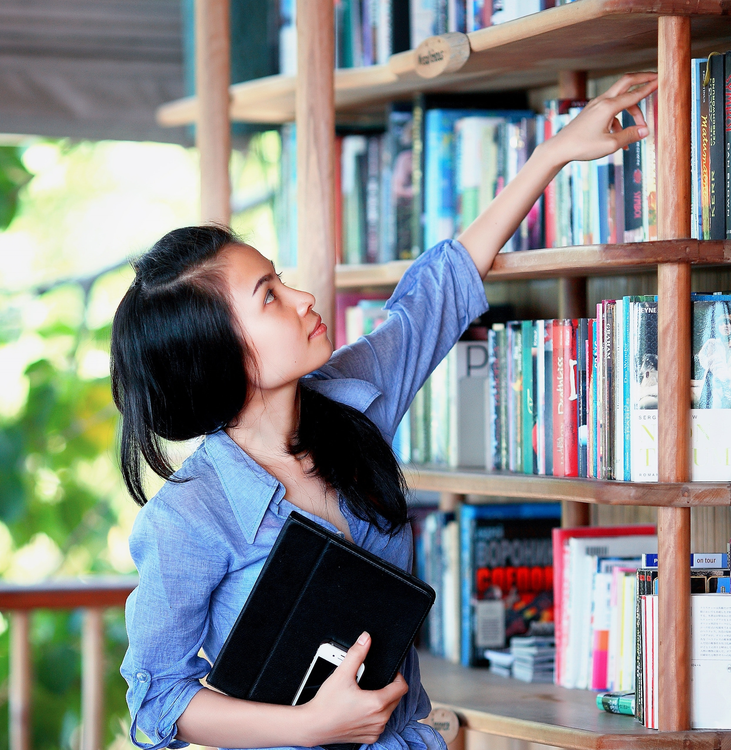 Asian teen picking book Pexels.jpg