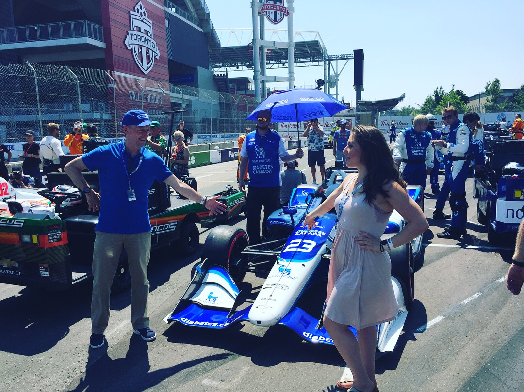 Dr. Deanna and Diabetes Canada's John Reidy posing at the Honda Indy right before T1D Indy racer Charlie Kimball took to the track.