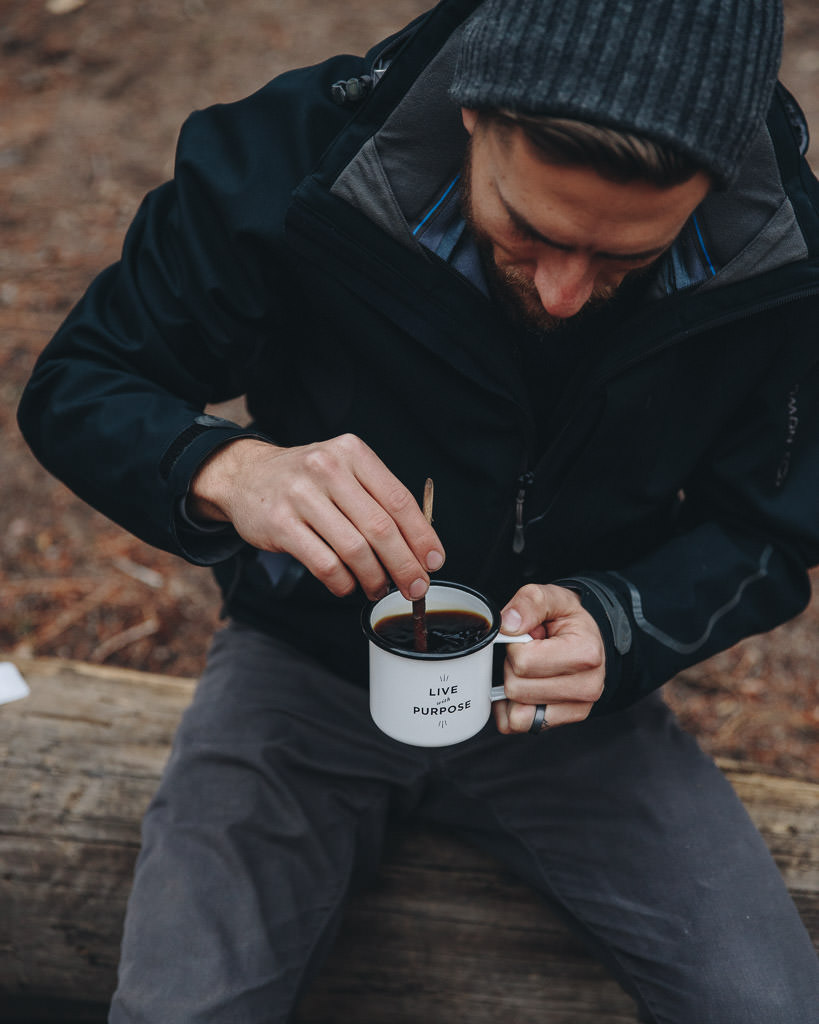 stirring instant coffee with a stick while backpacking
