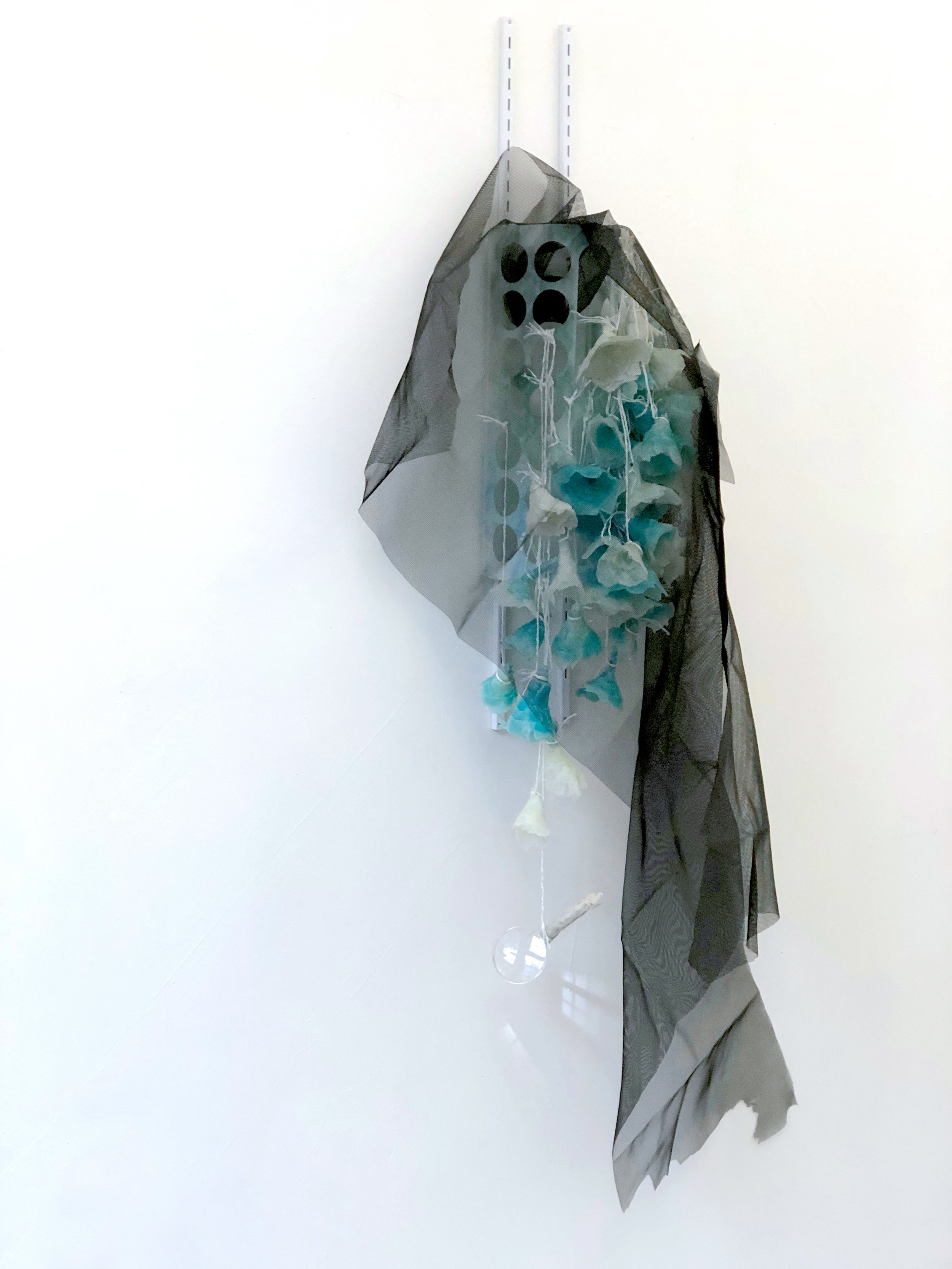 Shy Ghost  , 2018 Sheetrock joint compound gel, plastic bag dispense, wall bracket, polyester string, magnifying glass, charcoal fiberglass screen, lace, epoxy clay, acrylic and spray paint 67x30x17 inches