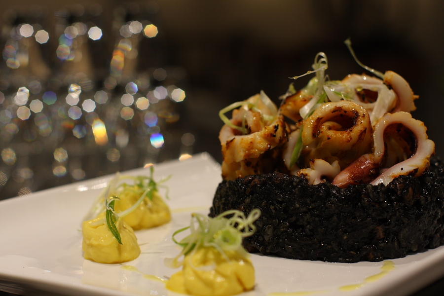 """As longer the rice is been cooked in the paella pan...  Black rice """"Arroz Negro"""", grilled squid, Spamish saffron mouse."""