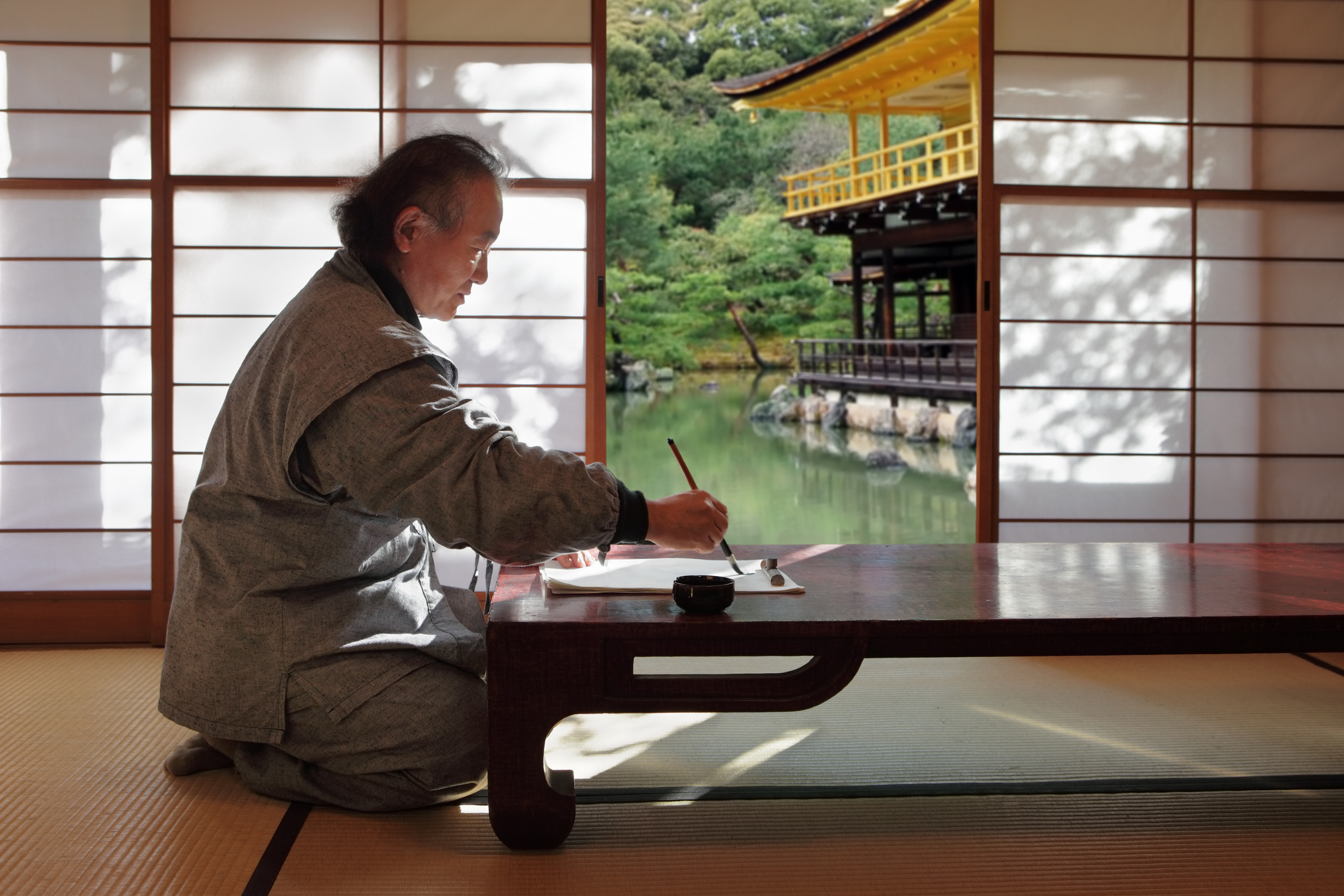 Traditional Japanese room with man sitting and brush painting.