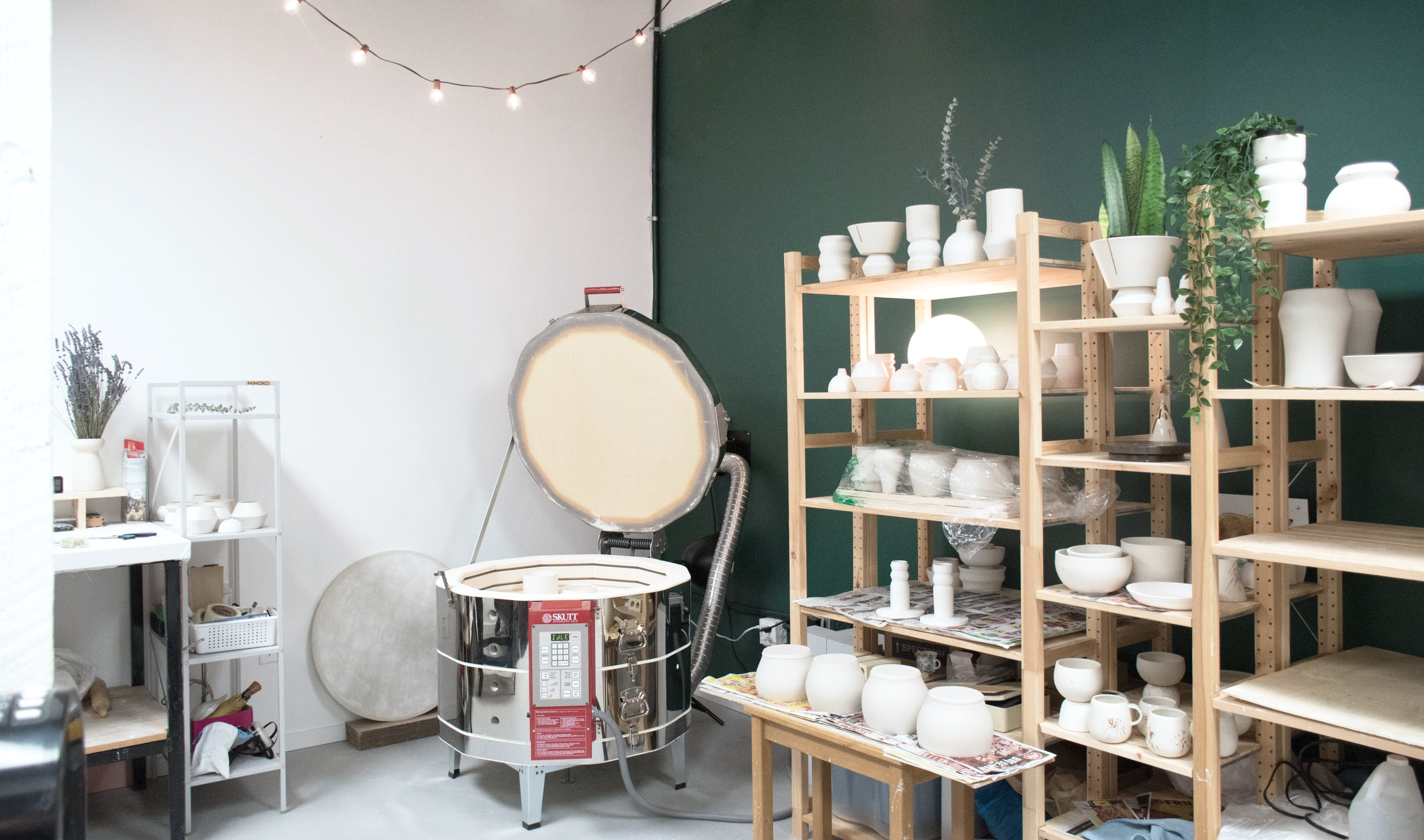 MiMOKO Ceramics studio with shelves full of pottery and open kiln.