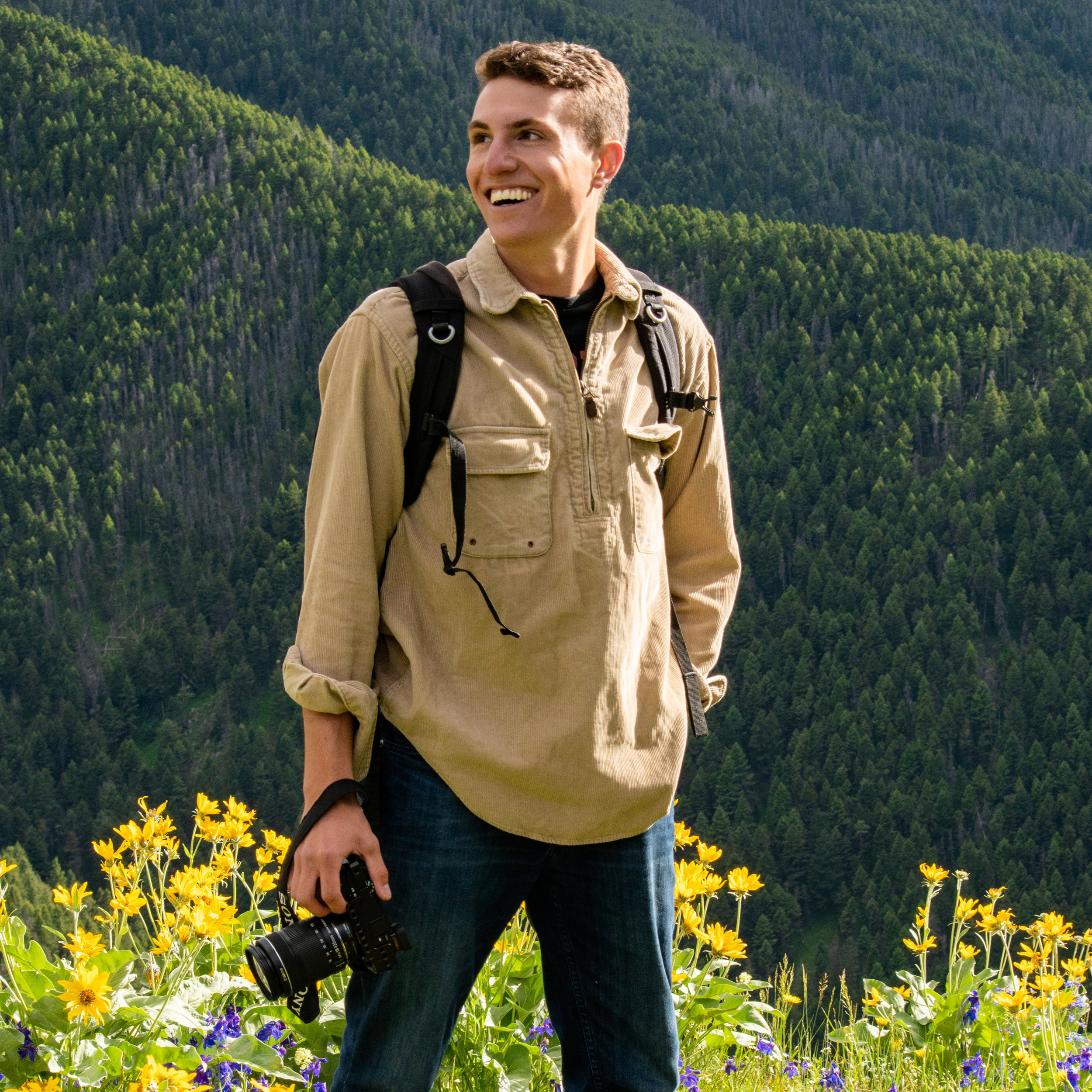 Eric Hyde of the Vativ Media team taking a photo with a DSLR camera in the Crazy Mountains in Montana