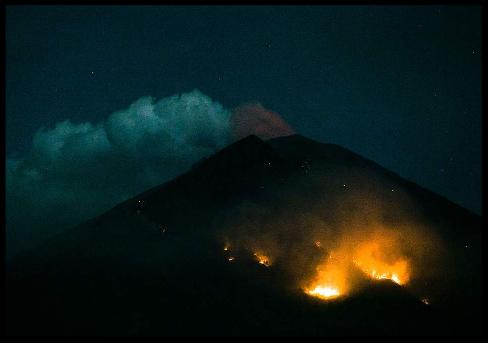 """Bali volcano: 'Flares of incandescent lava' shoot from Mount Agung after new eruption - A volcano on the Indonesian island of Bali has erupted, sending a 2,000-metre high column of thick ash spewing into the air and chunks of lava tumbling down its slopes.The Indonesian geological agency said a loud explosion was heard from Mount Agung just before 9pm local time, which lasted for more than seven minutes.Scientists at a volcano monitoring post witnessed """"flares of incandescent lava"""" reach 1.2 miles (2km) from the crater.The agency said the alert level for Agung has not been raised and the exclusion zone around the crater remains at two-and-a-half miles (4km)...Read More"""