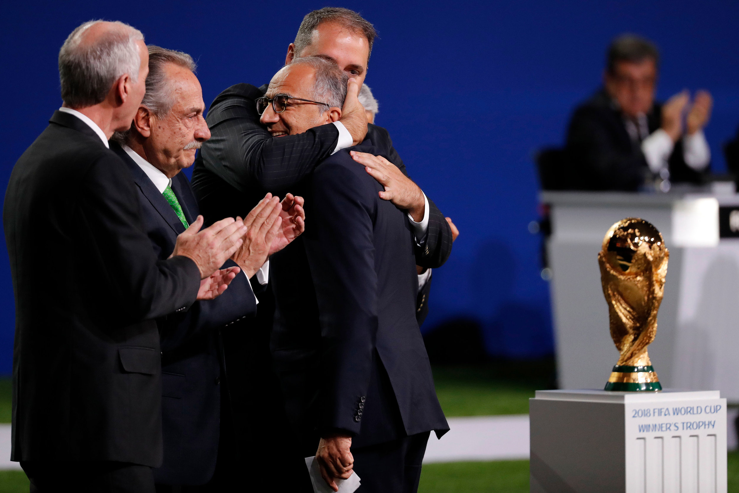 The leaders of professional football in Mexico, Canada, and the USA embrace following their bid for the 2026 World Cup being granted.
