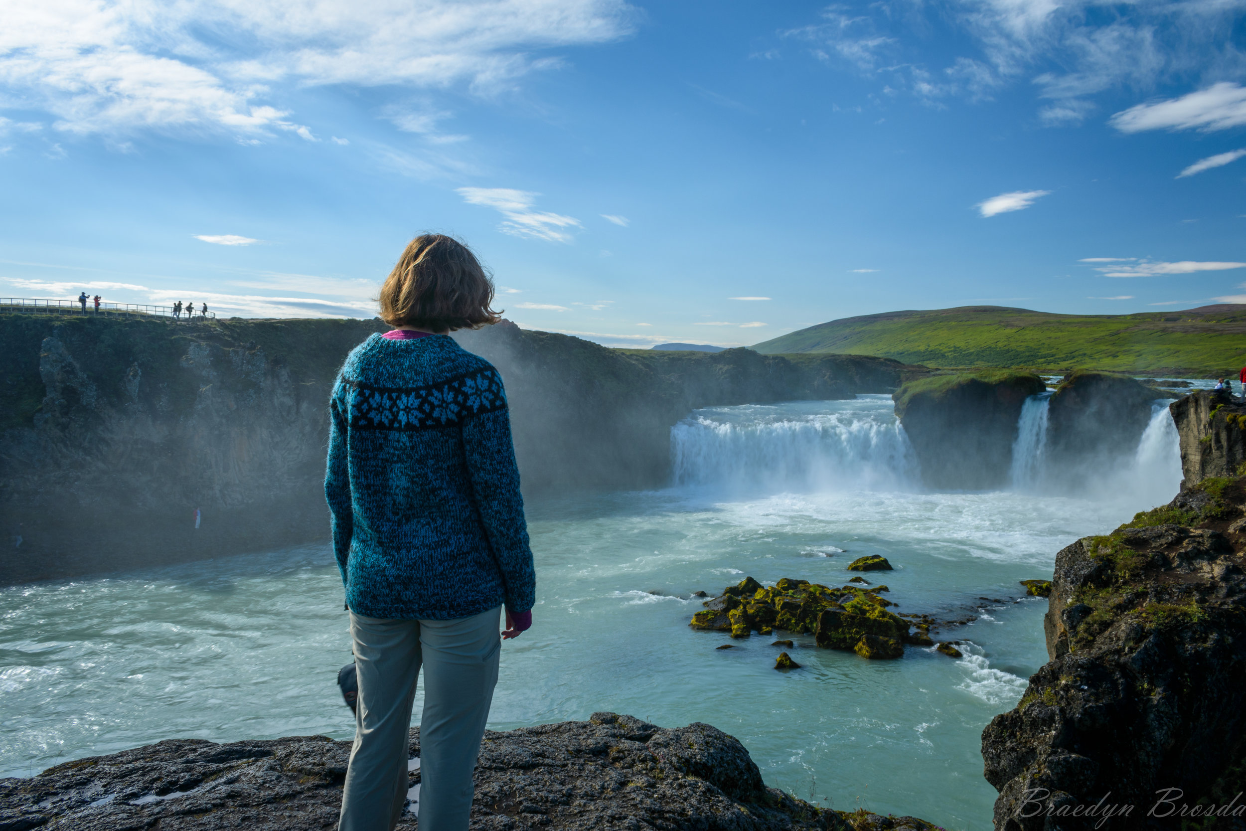 Sarah and her Icelandic sweater in front of an Icelandic waterfall