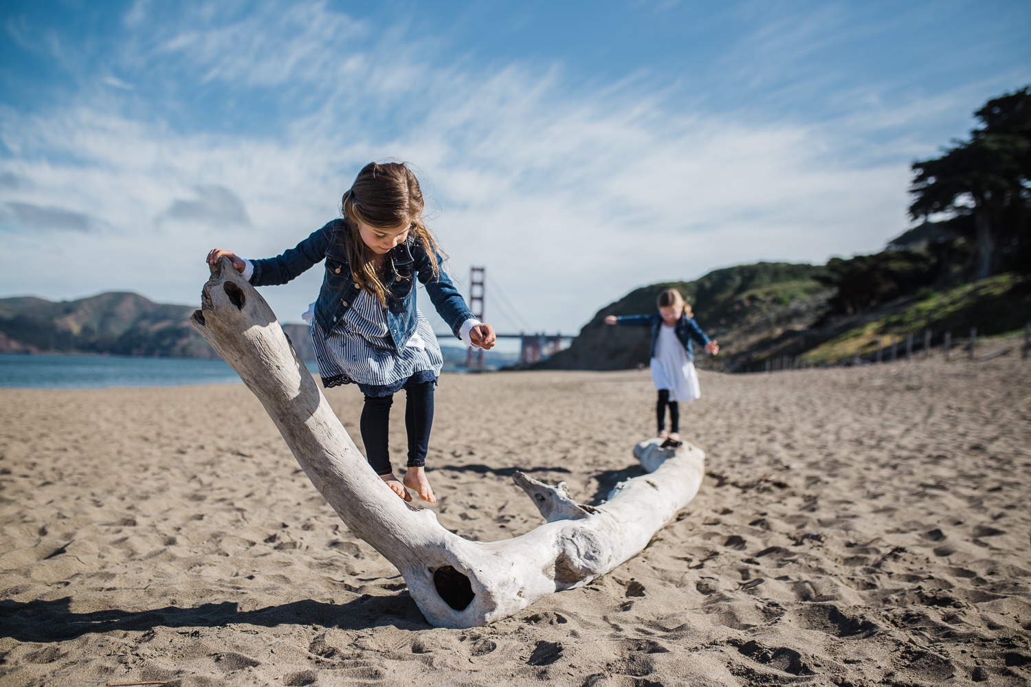 five year old sisters playing on driftwood together on Baker beach {San Francisco Family Photographer}