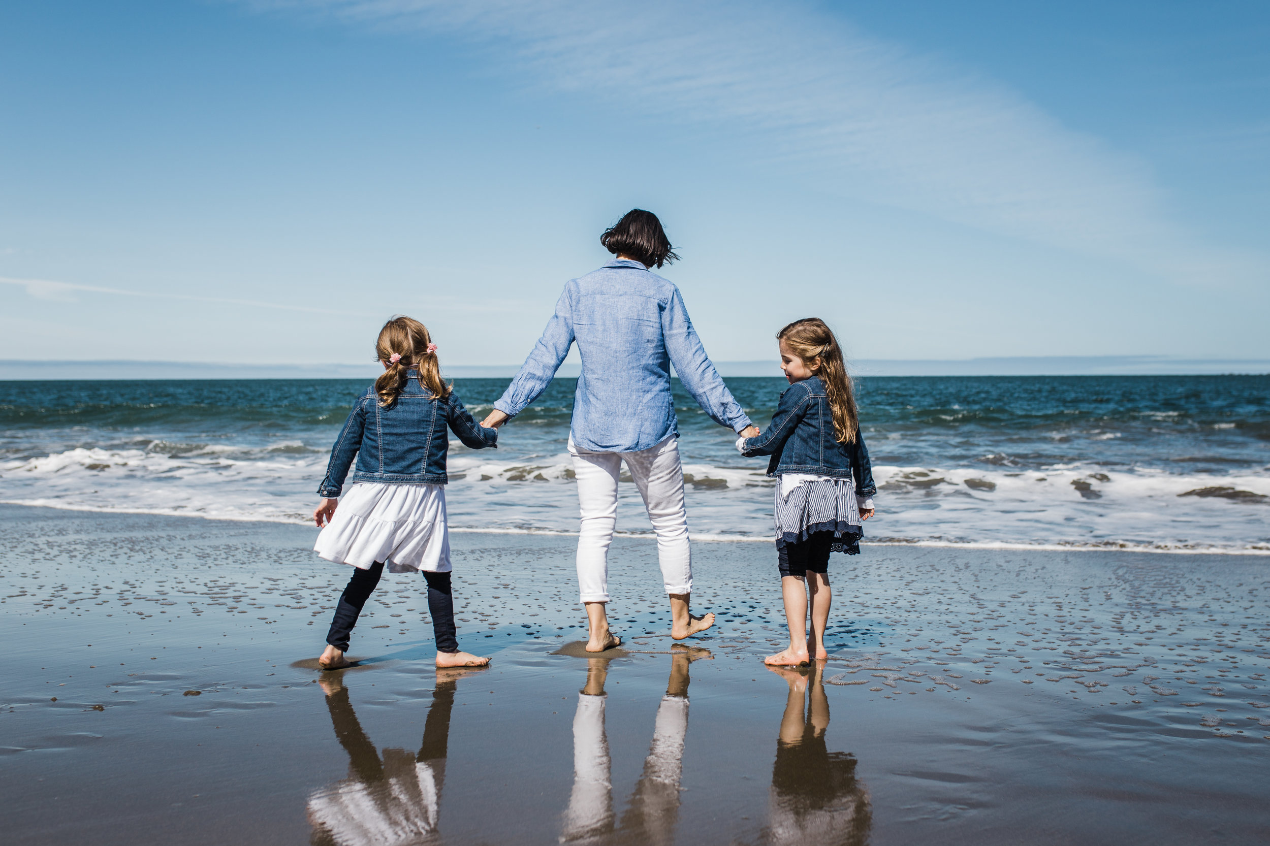 mom and her twin five year old girls holding hands and walking on Baker Beach towards the water {San Francisco Family Photographer}