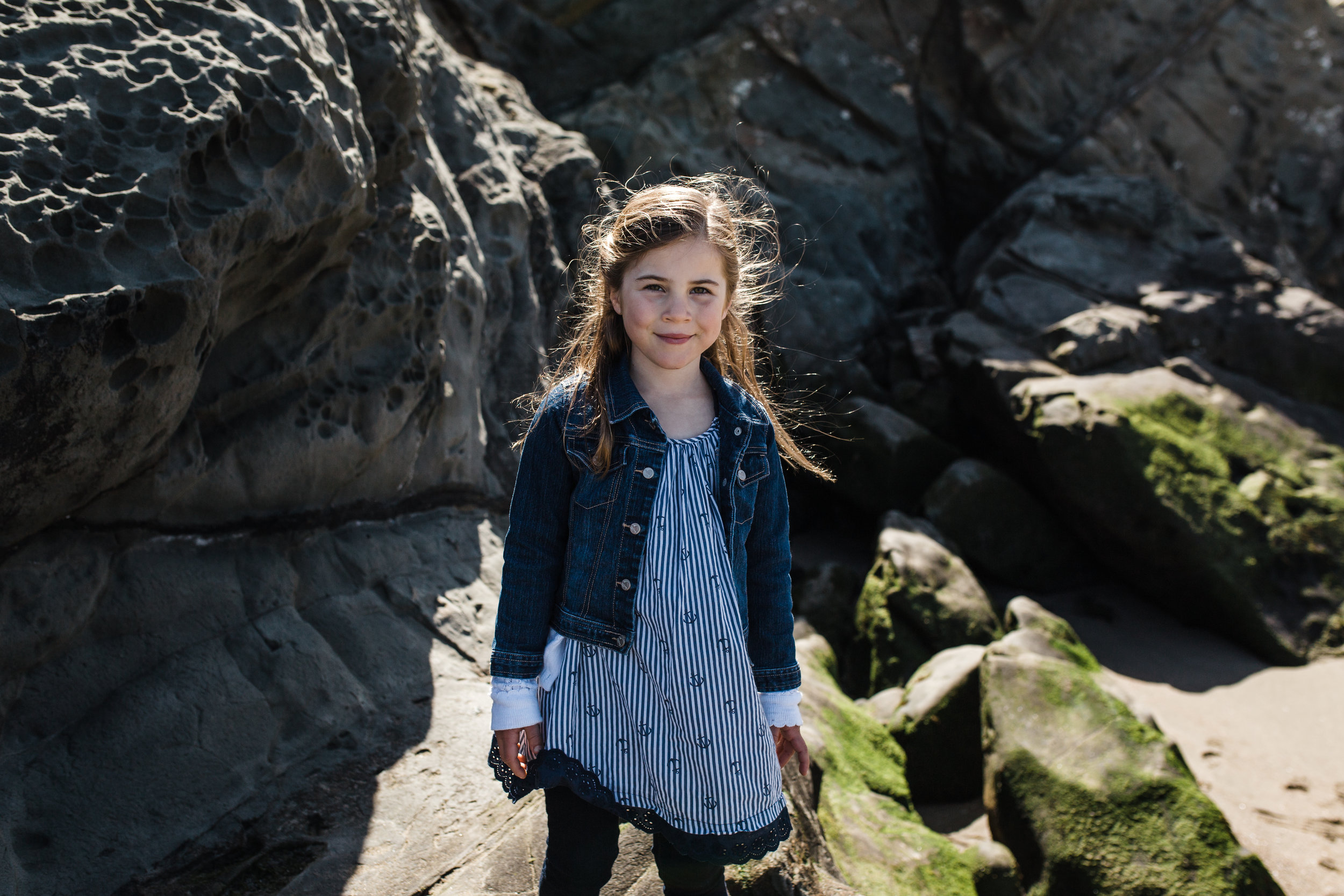 Portrait of a 5 year old girl standing on the rocks at Baker Beach {San Francisco Family Photography}