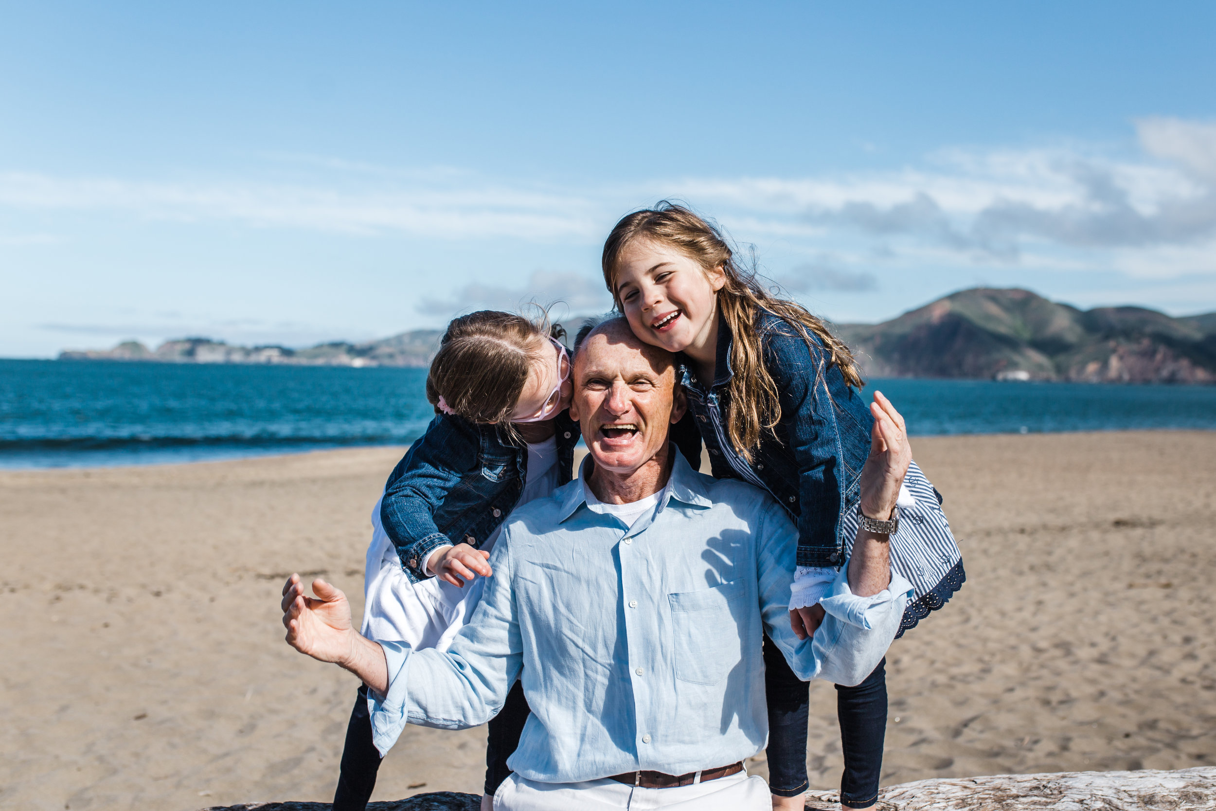 dad sitting on the beach with his twin five year old girls while girls each hug and kiss him from either side of him {Bay Area Family Photography}