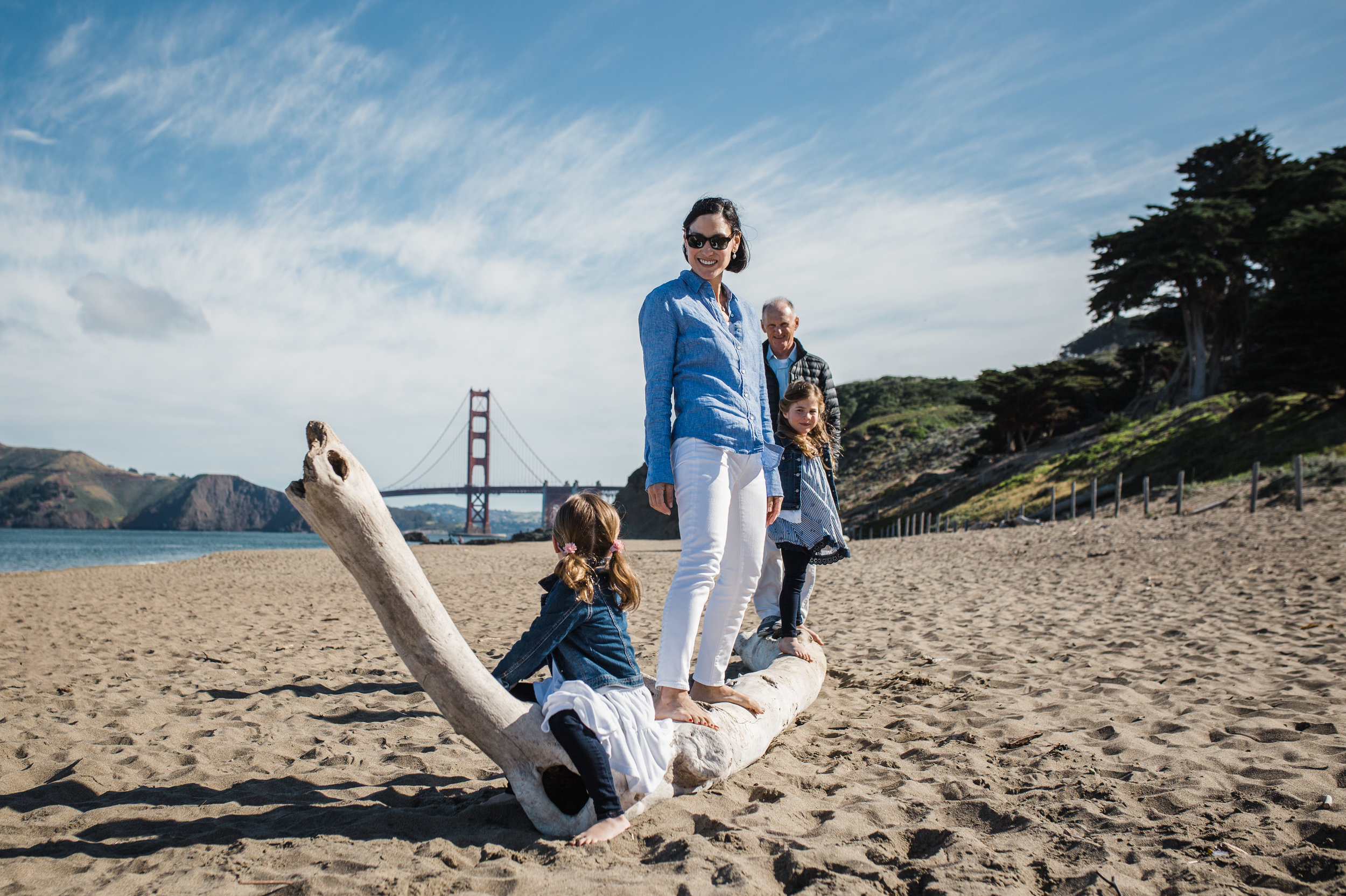 Family of 4 standing on driftwood at Baker Beach beach {San Francisco Family Photographer}