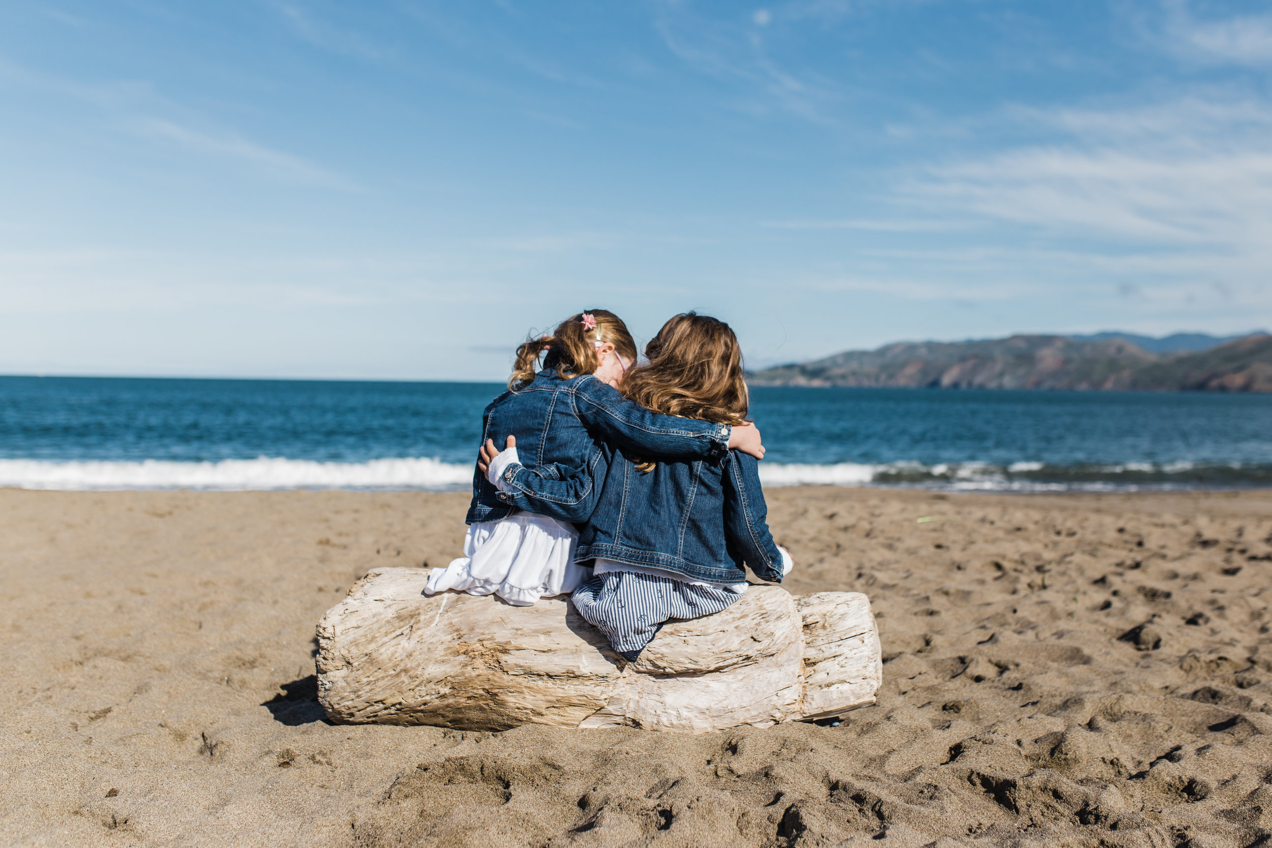 five year old twin sisters sitting on a piece of driftwood on Baker Beach with their arms wrapped around each other {San Francisco Family Photographer}