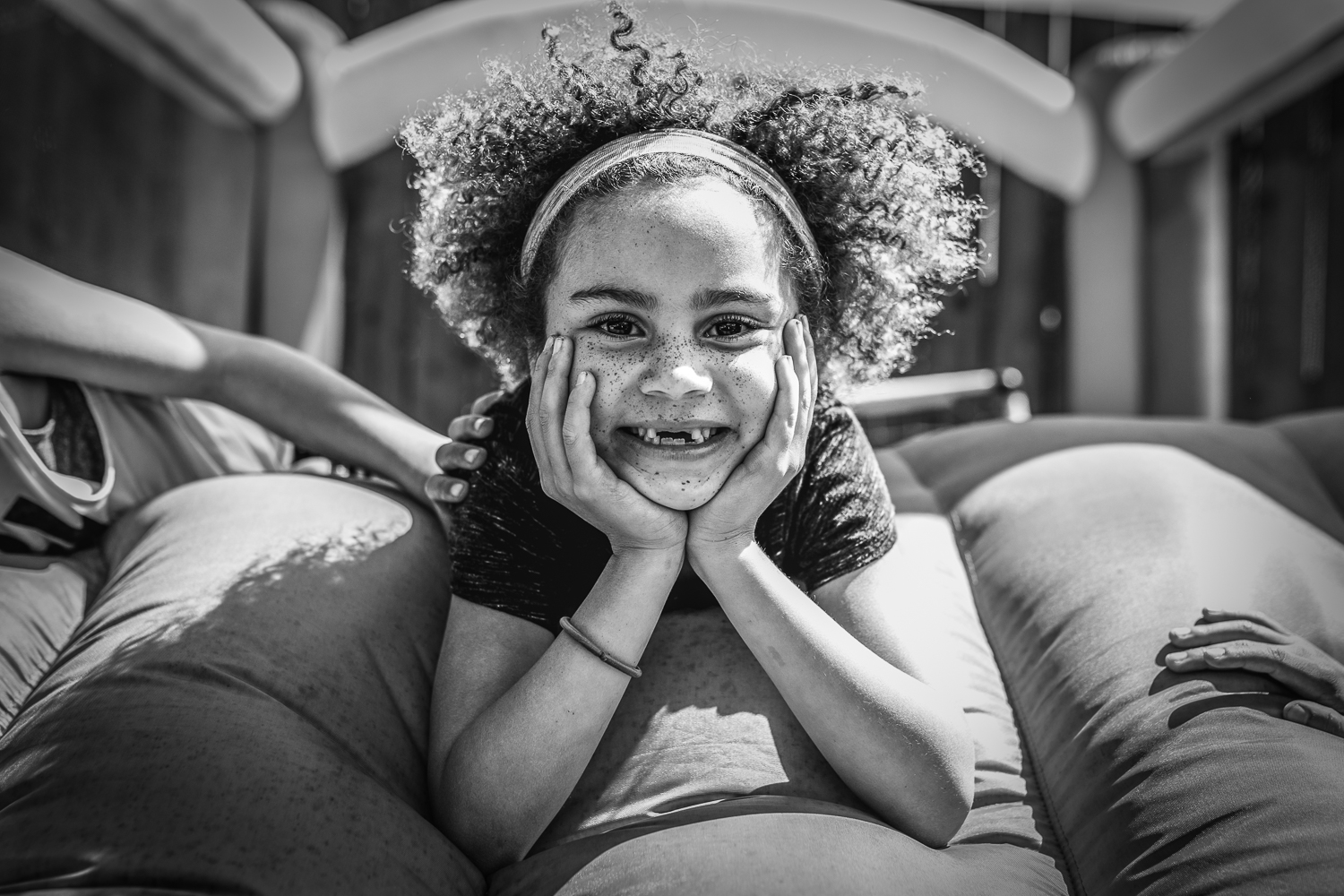 Girl looking at the camera and smiling while laying in bouncy house {San Francisco Family Photographer}