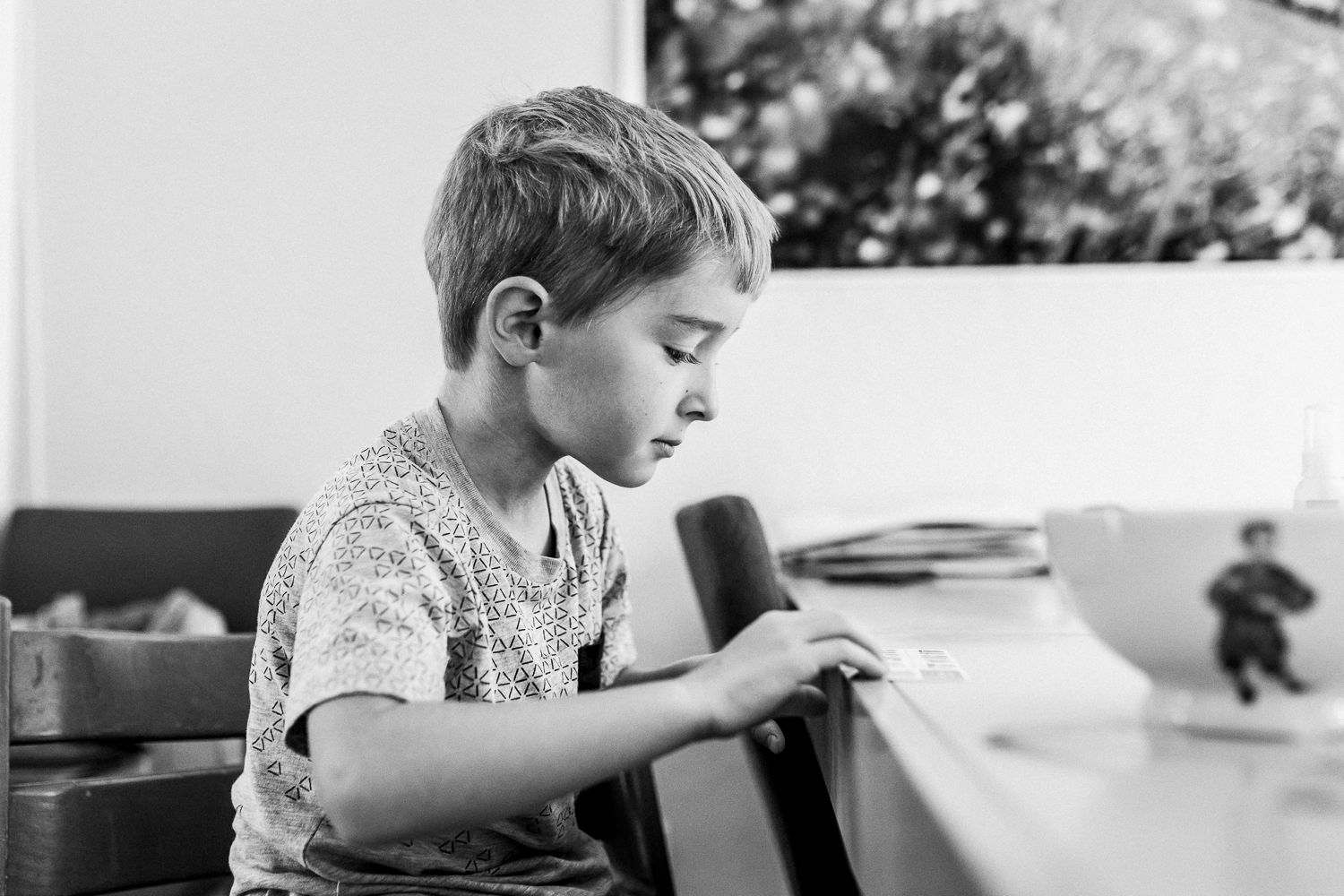 five year old boy sitting at the kitchen table looking at a paper {San Francisco lifestyle Family Photographer}