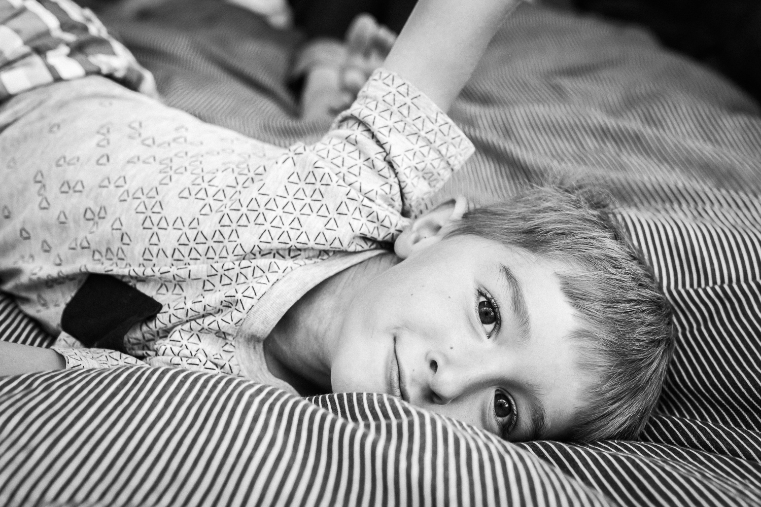 five year old boy laying on his parent's bed and smiling at the camera {San Francisco in-home Family Photographer}