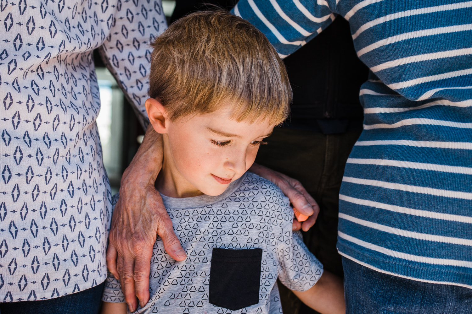 close up of five year old boy standing next to his mother and grandmother with their hands touching his back {San Francisco in-home Family Photographer}