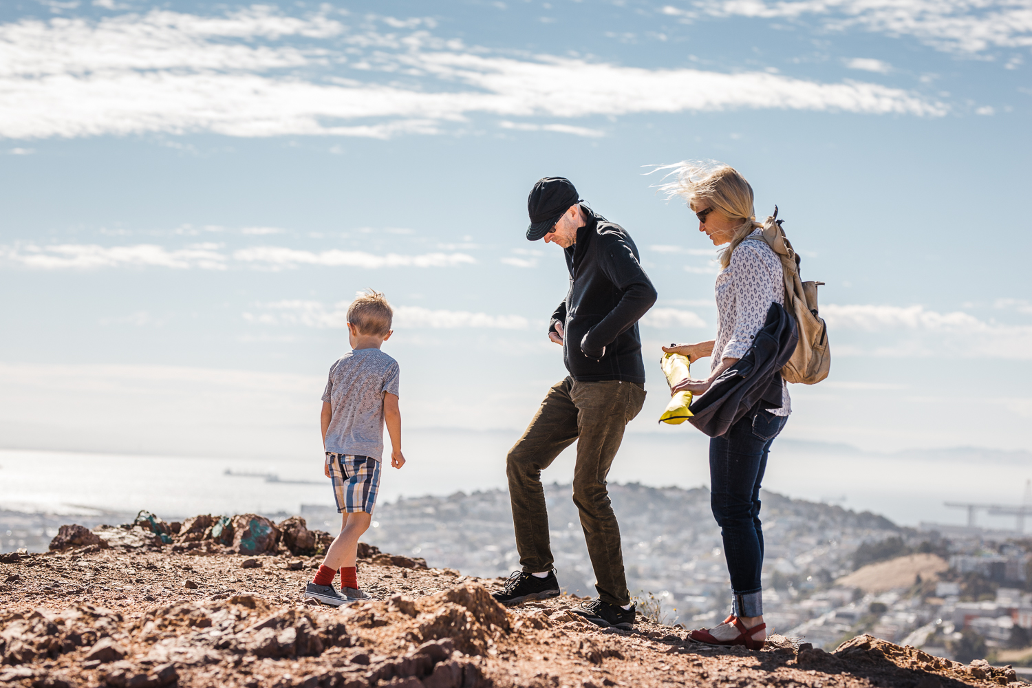 Family of three up on a hill overlooking San Francisco looking at the view during family session {San Francisco Family Photography}