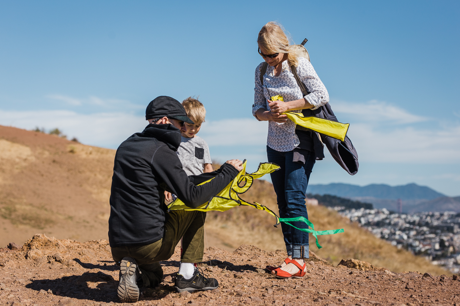 Family of three setting up to fly a kite overlooking the city {San Francisco Lifestyle Photographer}