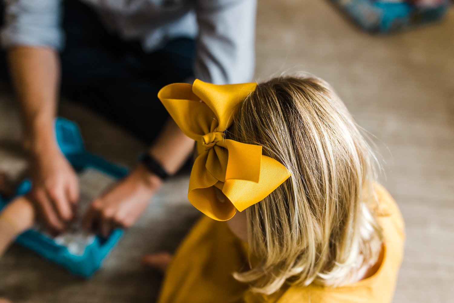 Birdseye photo of a two year old little girl's big yellow bow while she plays a game with her family {East Bay in-home lifestyle Family Photographer}