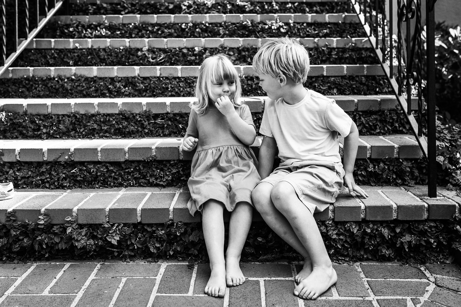black and white picture of a five year old brother and three year old sister sitting on the from stairs of their house looking at each other {East Bay in-home lifestyle Family Photographer}