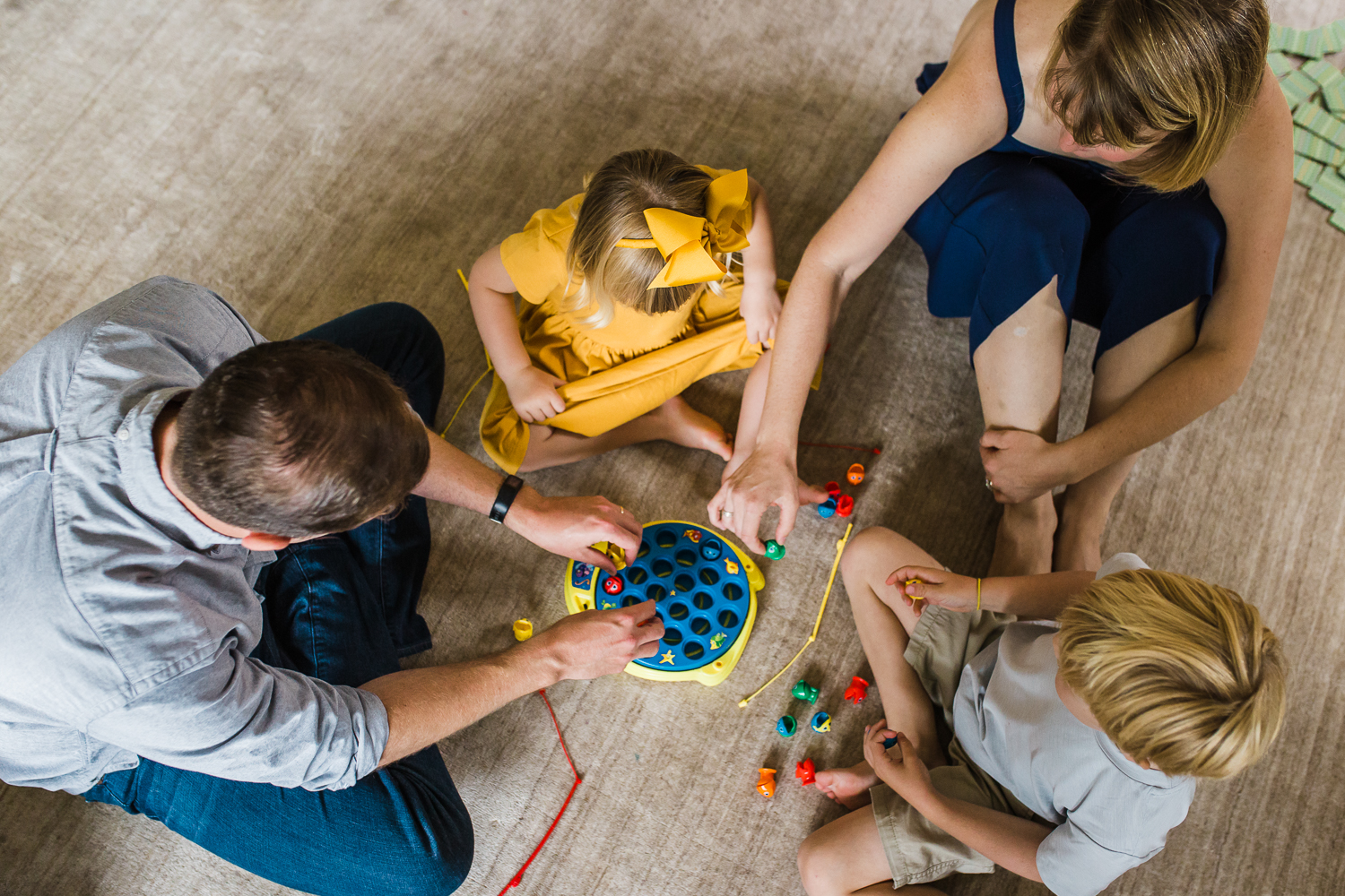 birdseye view of a family of four playing a board game together {East Bay in-home lifestyle Family Photographer}