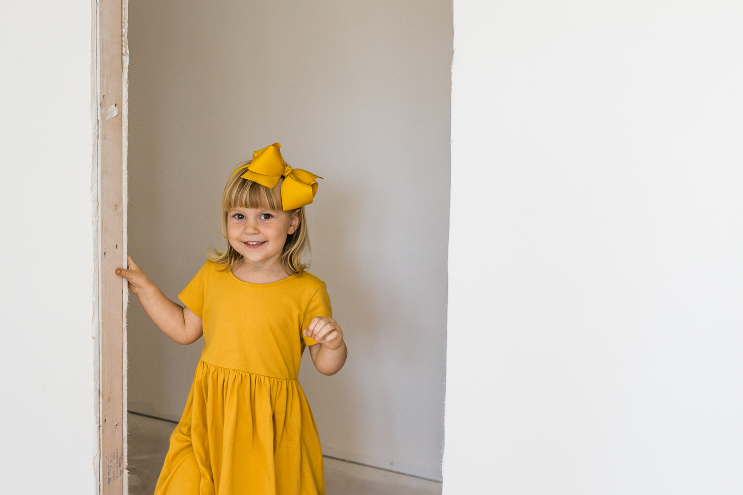 three year old little girl in a yellow dress standing in a doorway and smiling in her new house {Oakland Family Photography}