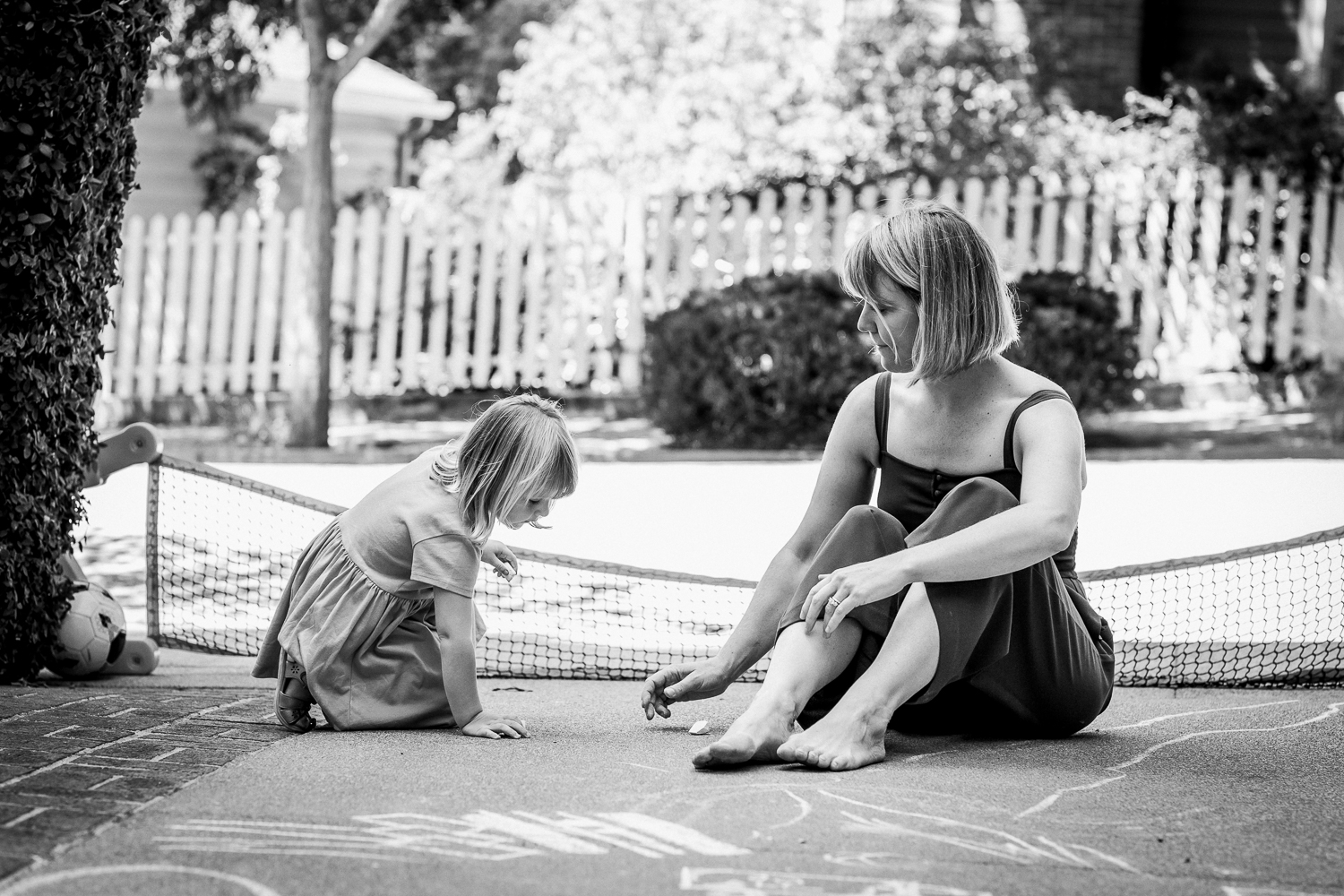 black and white picture of mom and three year old daughter drawing with sidewalk chalk on the driveway of their house {Oakland in-home lifestyle Family Photographer}