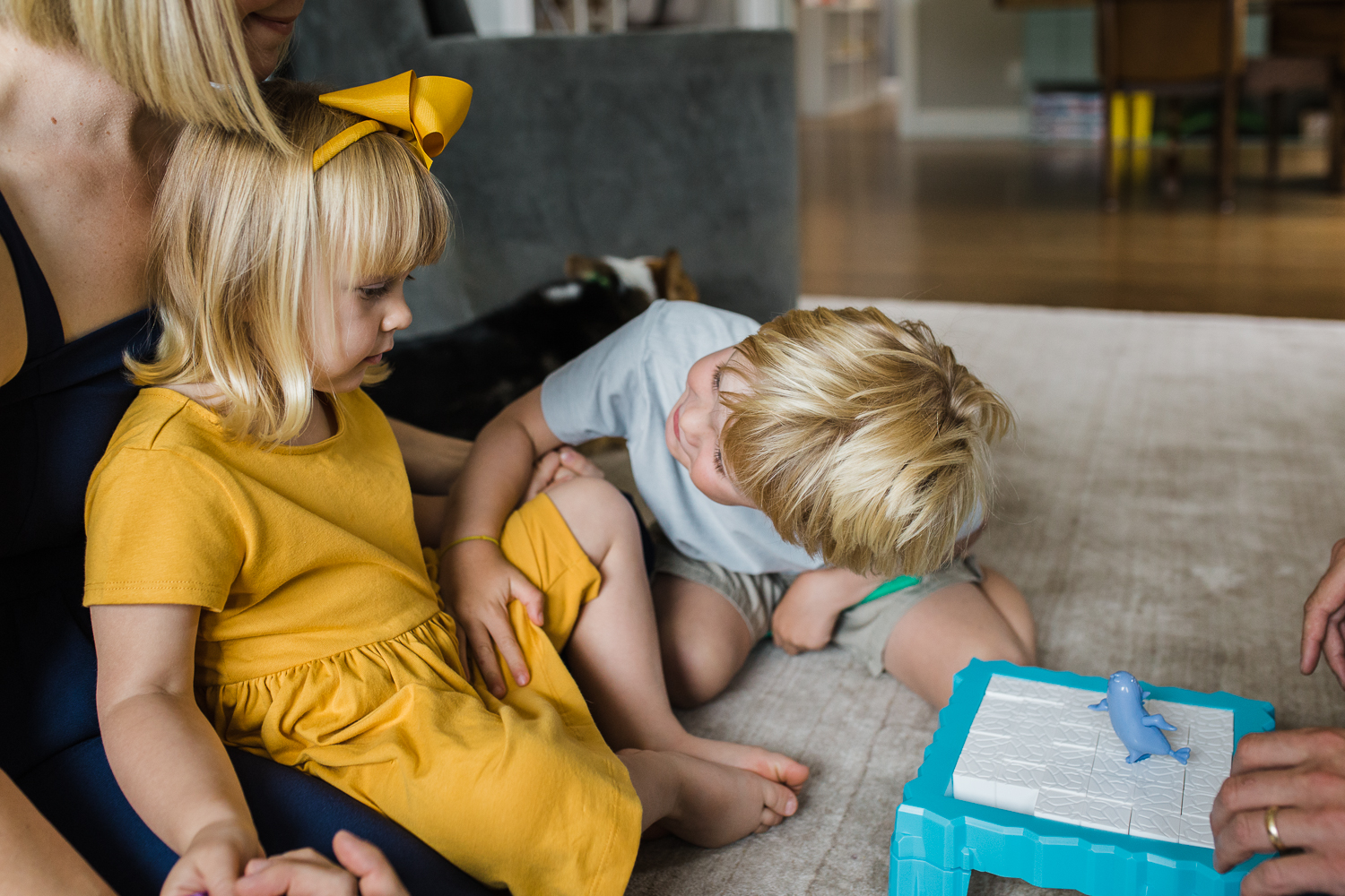 five year old brother looking at his two year old sister trying to get her attention while they are playing a game together with Mom and Dad {Oakland in-home lifestyle Family Photographer}