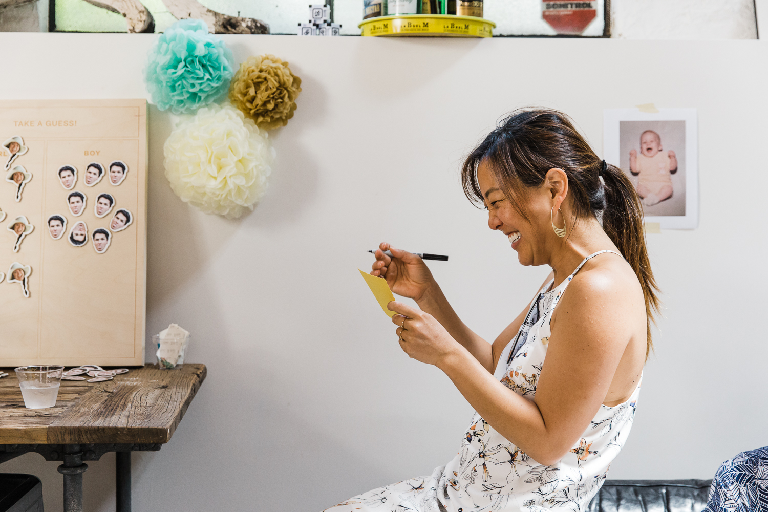 A woman smiling as she writes advice to her friend at a gender reveal party {San Francisco Newborn Photographer}