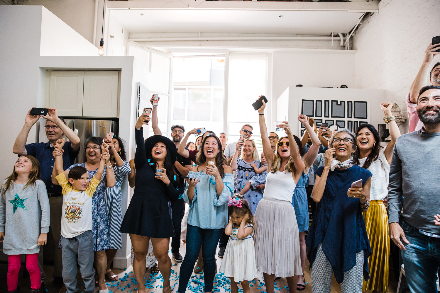 Excited family and friends celebrating when they find out it's a boy at a gender reveal party {San Francisco Newborn Photographer}